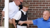 Police lead suspected shooter Dylann Roof, 21, into the courthouse in Shelby, North Carolina on June 18, 2015. Roof, a 21-year-old with a criminal record, is accused of killing nine people at a Bible-study meeting in a historic African-American church in