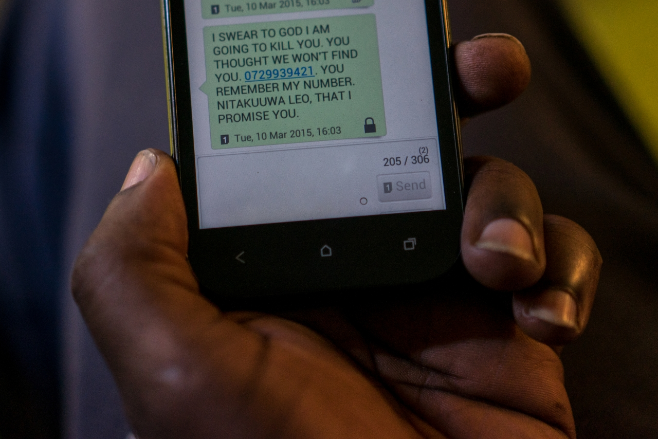 Mbonimpa, 27, a gay man from the Democratic Republic of Congo shows one of the death threats a friend of his, a Ugandan LGBT refugee named David, has received on his cell phone