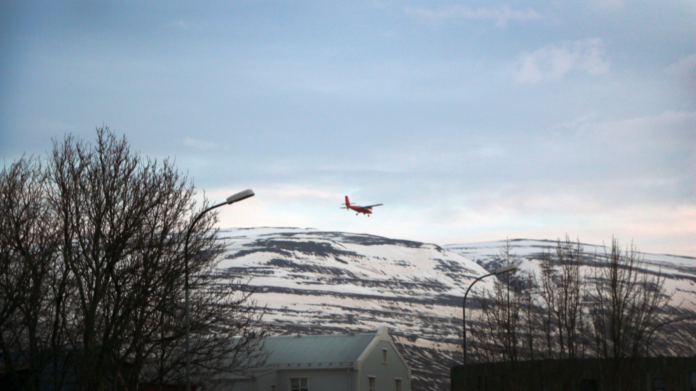 A red plane is seen in the sky above snow covered mountains and a small village