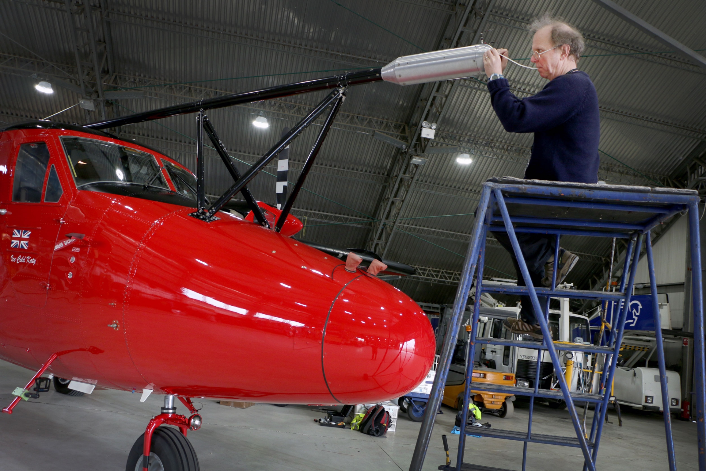 A man on a ladder works on a cherry red science airplane