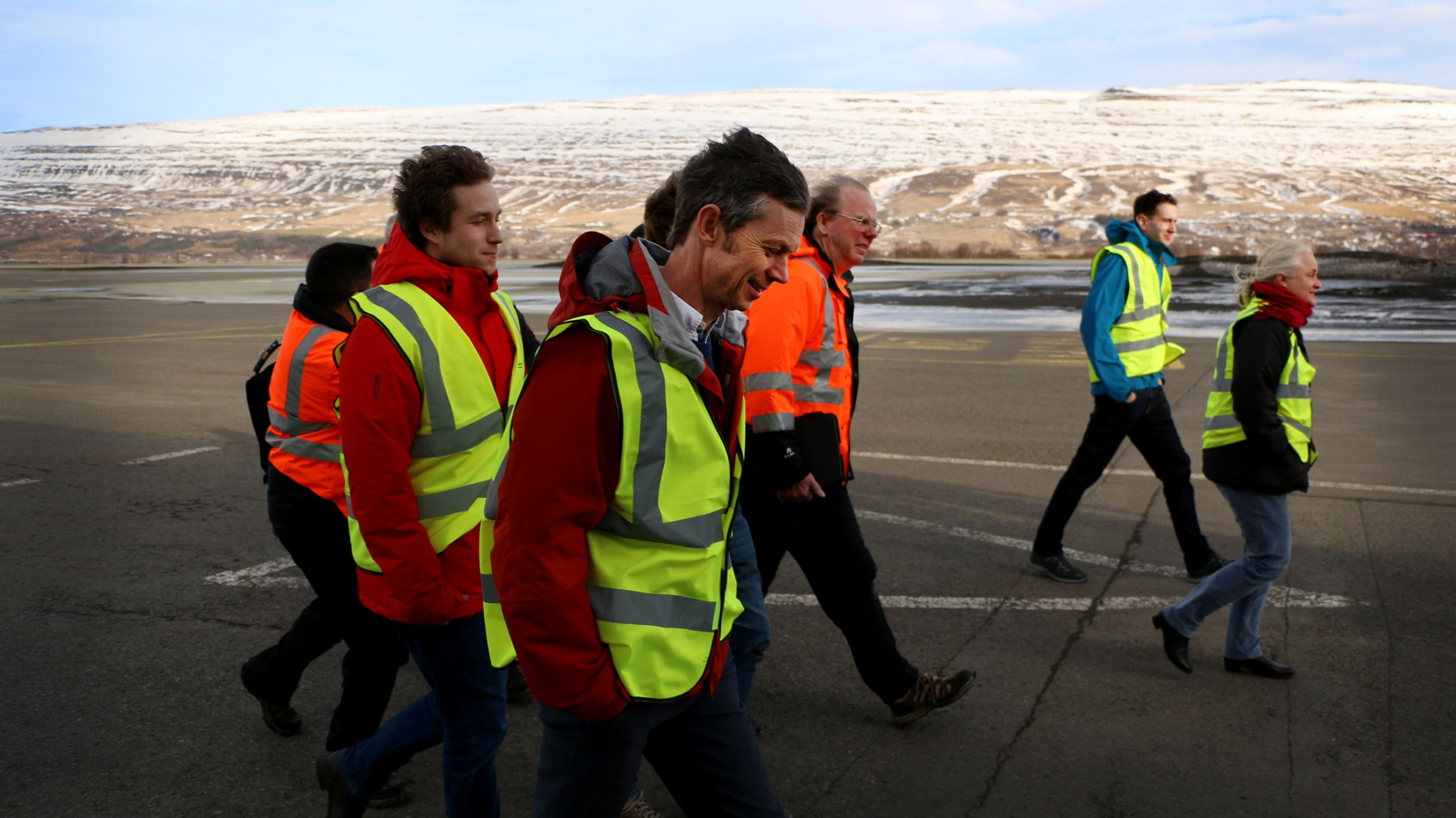A group of people in bright safety vests walk through the wind on a tarmac.