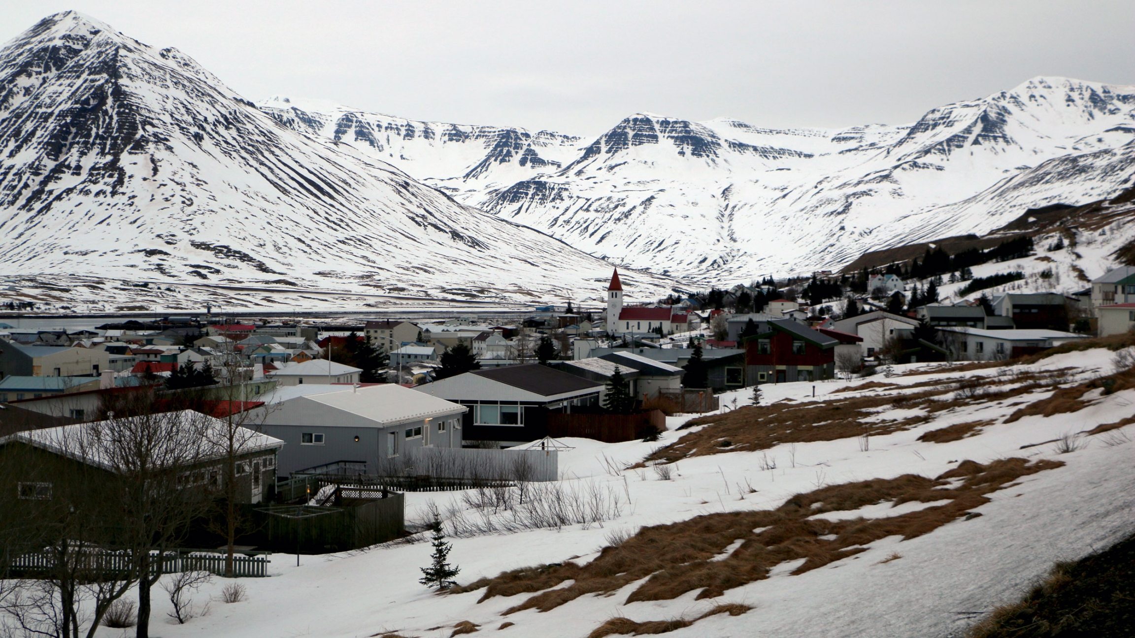 A town is blanketed in snow and flanked by a mountain