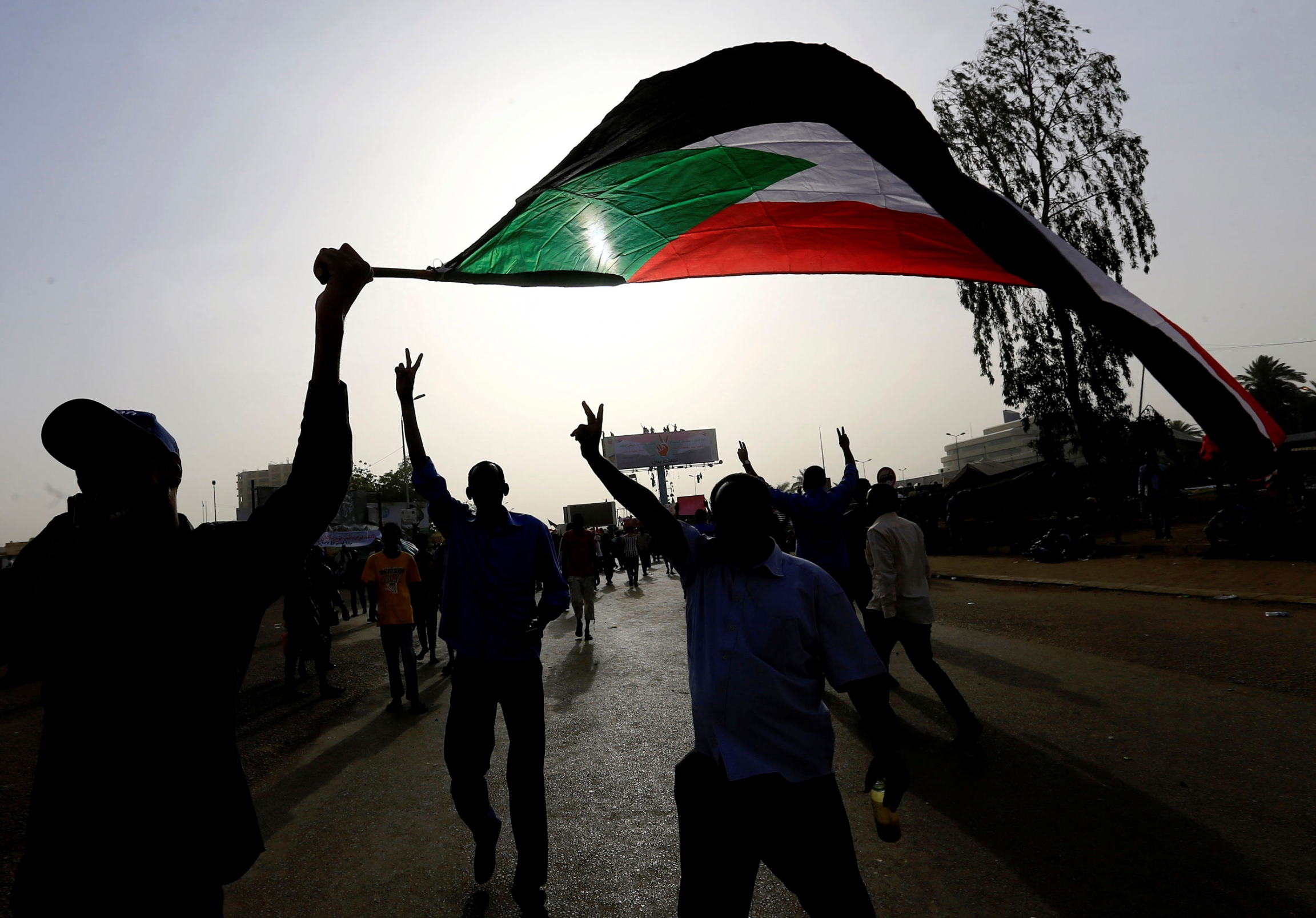 People hold their hands in the air and wave a large Sudanese flag. They are backlit by the sun.
