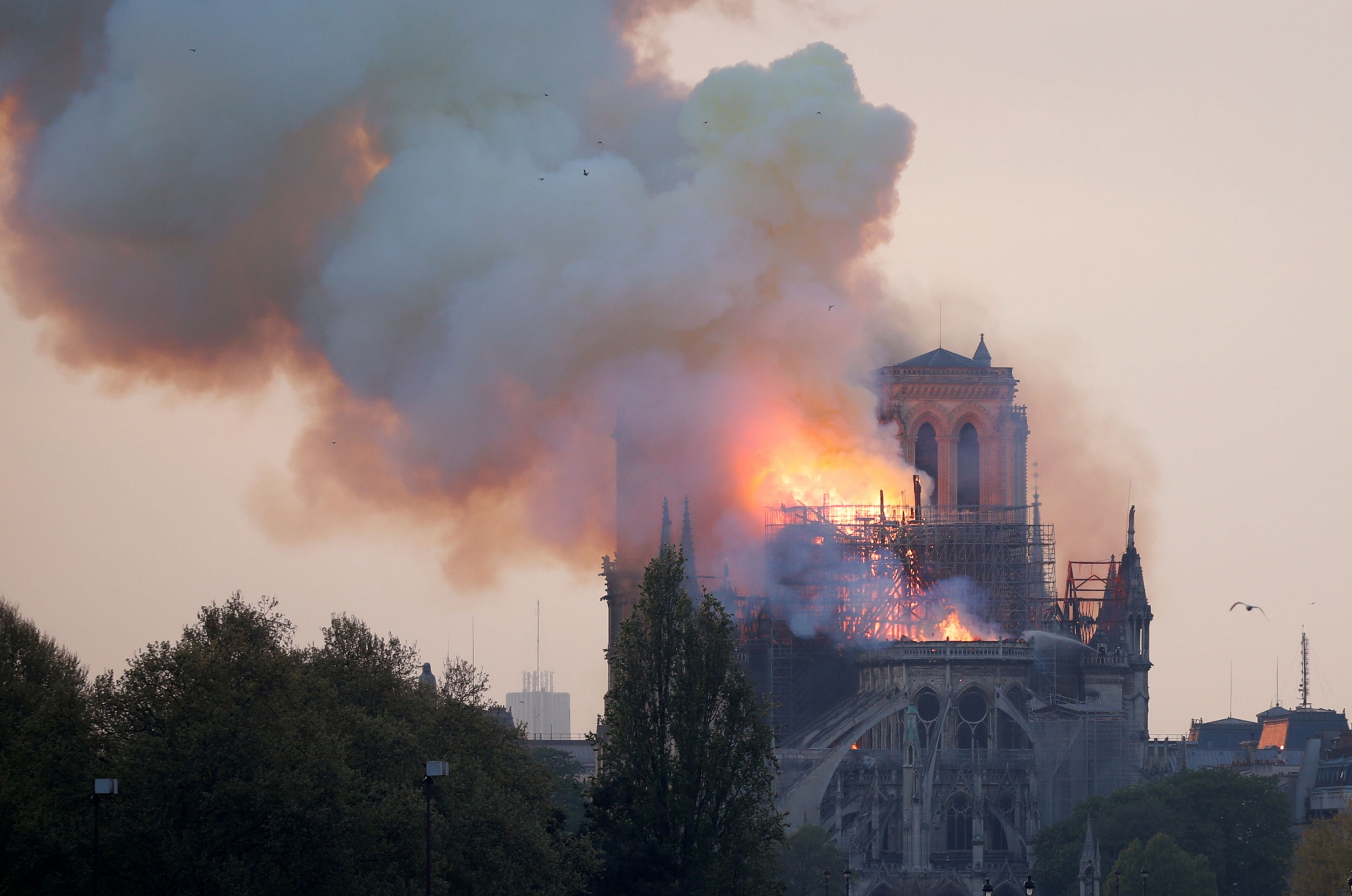 A photo shows the top of the Notre Dame cathedral on fire.