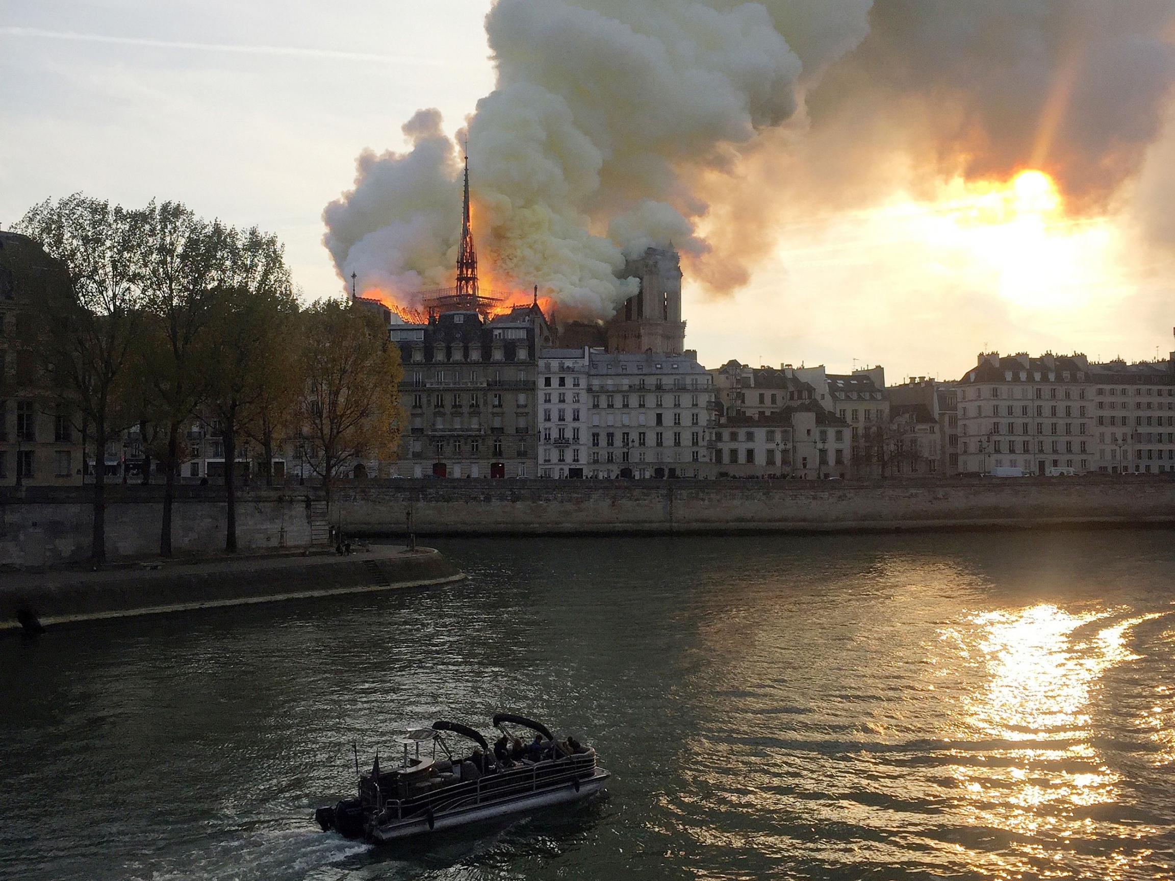White smoke billows from the top of Notre Dame, see over the river Seine while a boat passes by