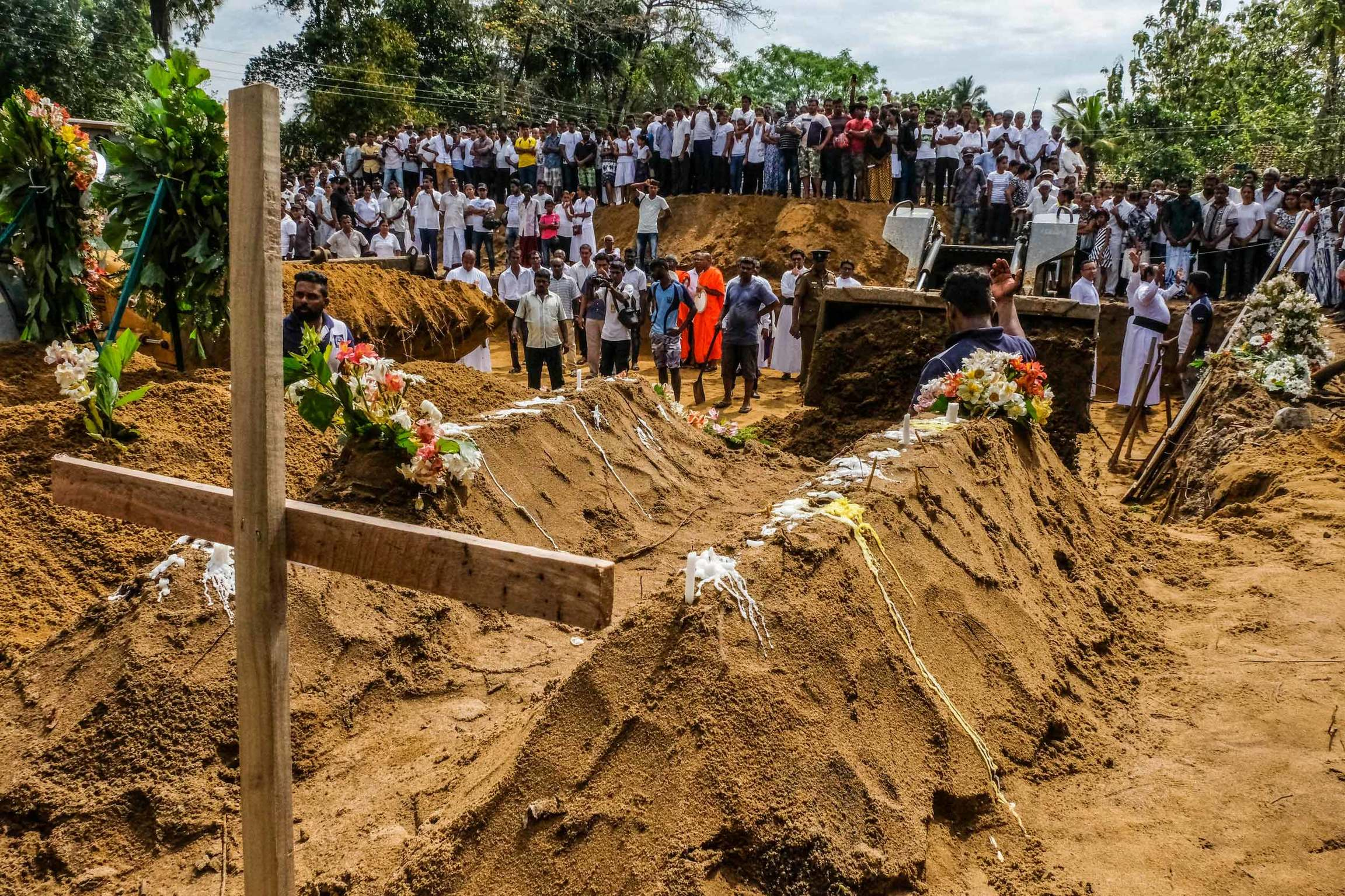 A crowd of people watch as a backhoe moves dirt over caskets during a mass funeral