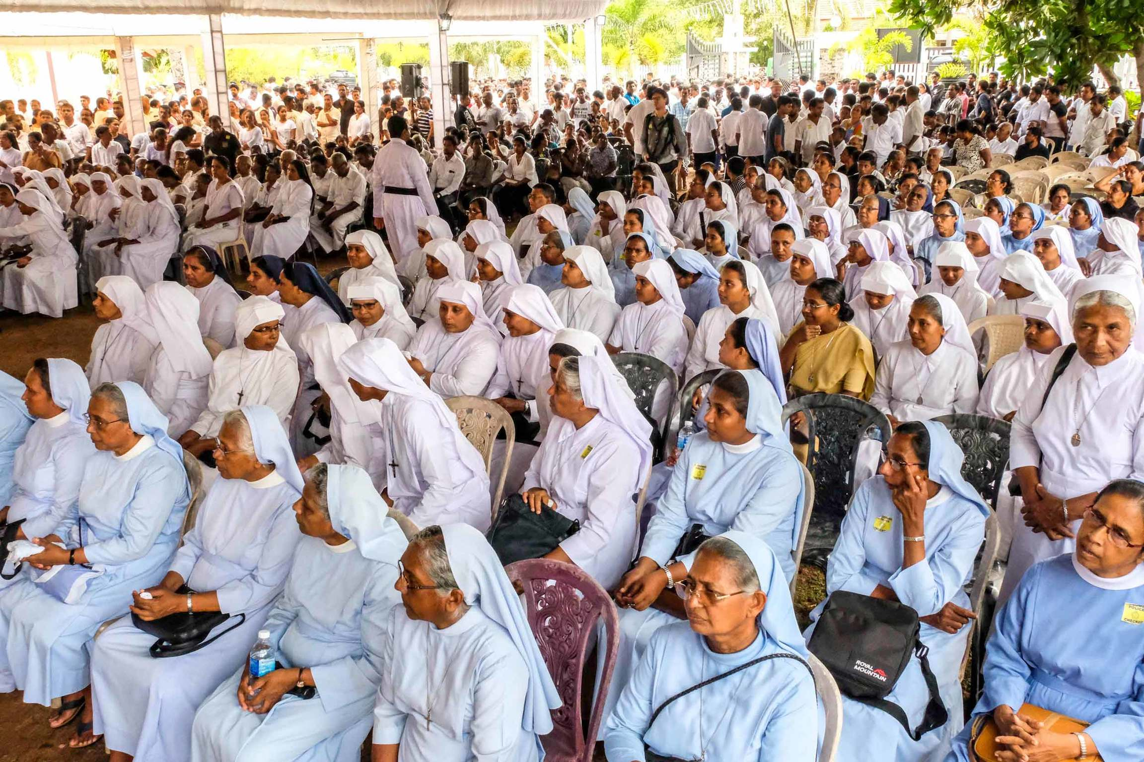 Nuns and other worshippers sit under a large tent