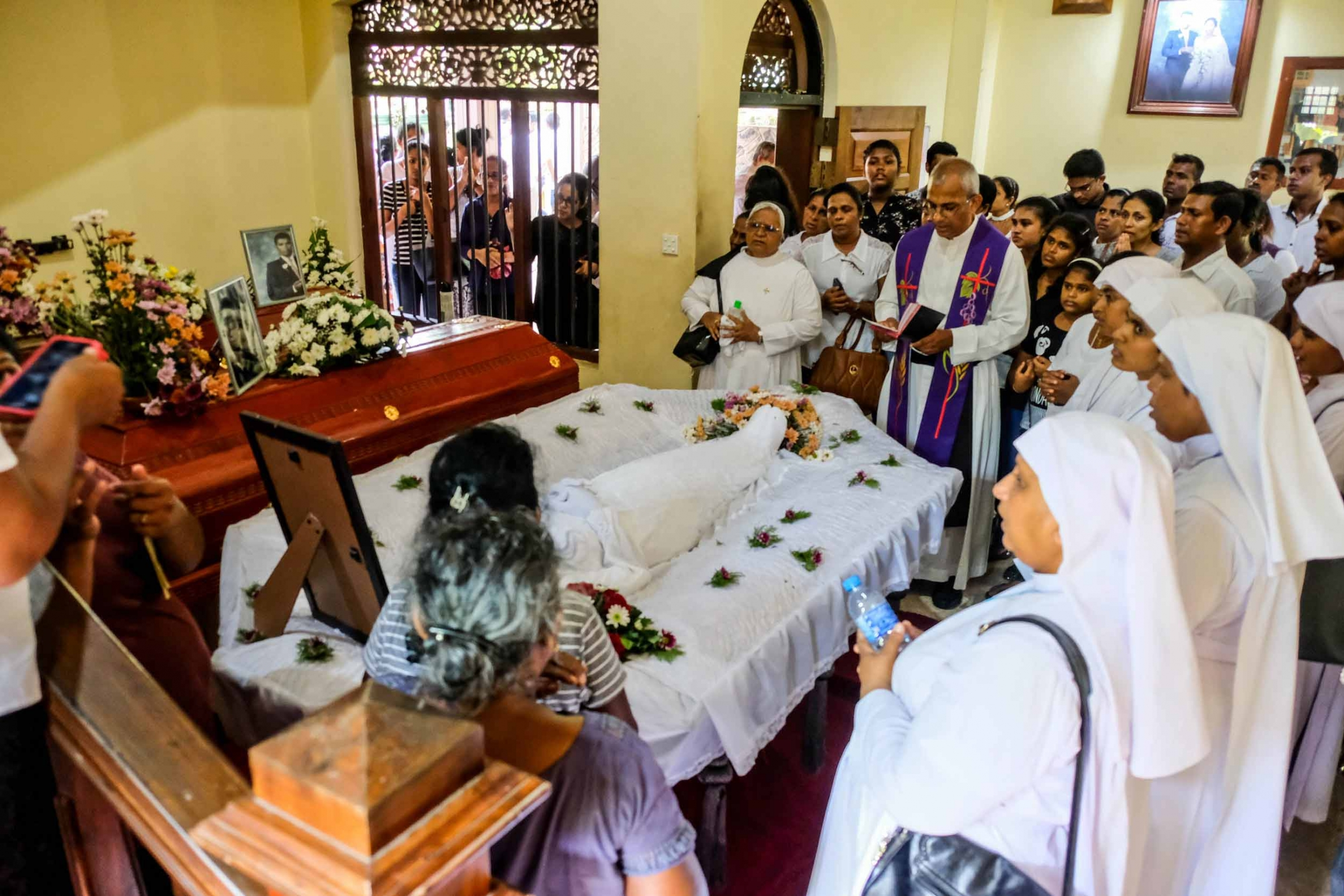 Family and friends gather around a casket in a small home while a priest reads a service