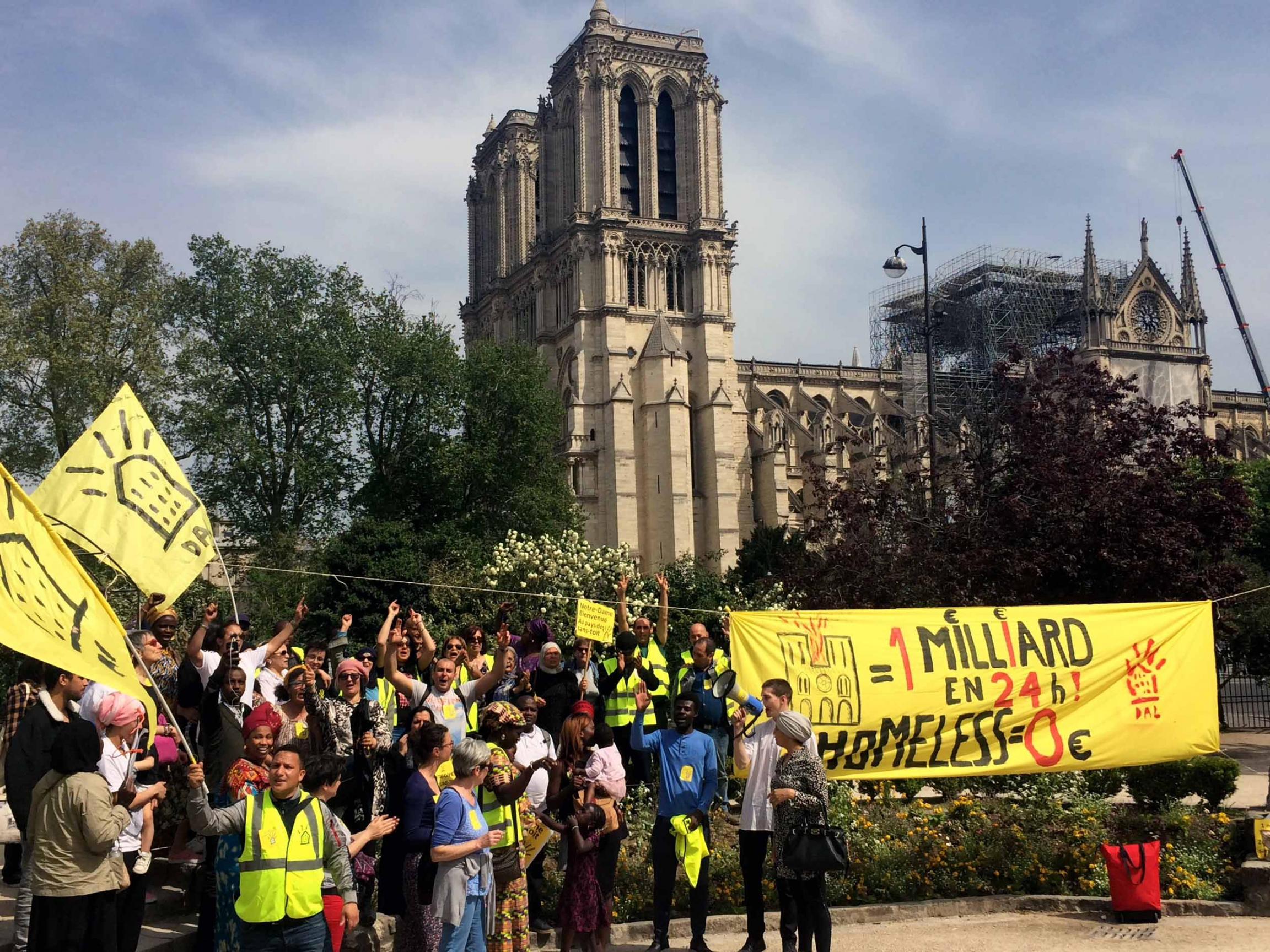 A crowd of people hold yellow signs and a banner. The towers of Notre-Dame are visible in the background.