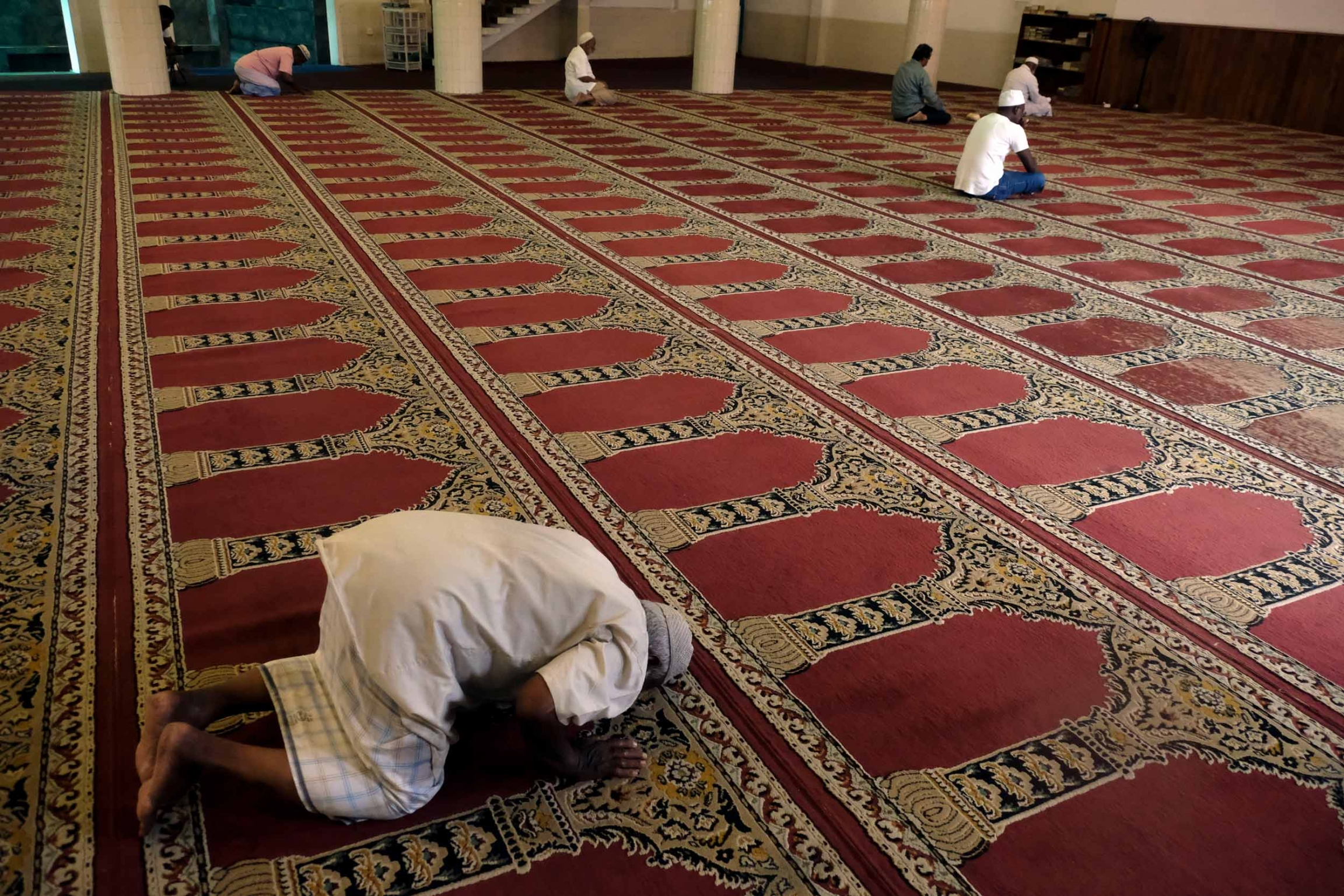 A few men are praying in a mosque