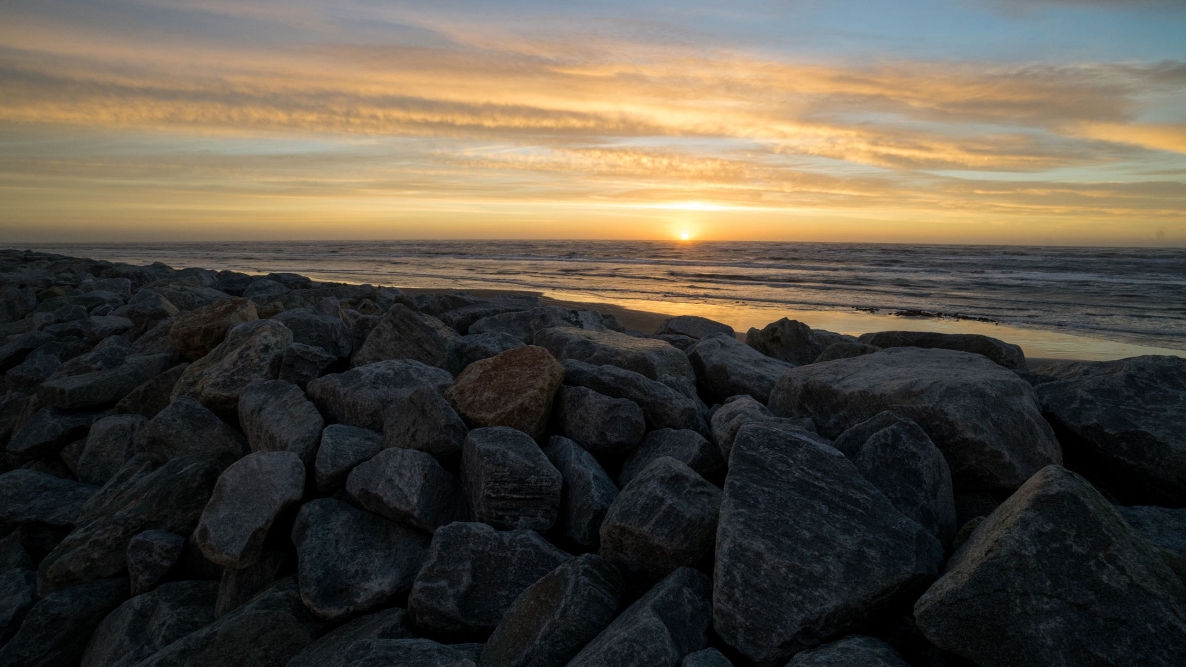 The sun sets into the ocean along a rocky seawall