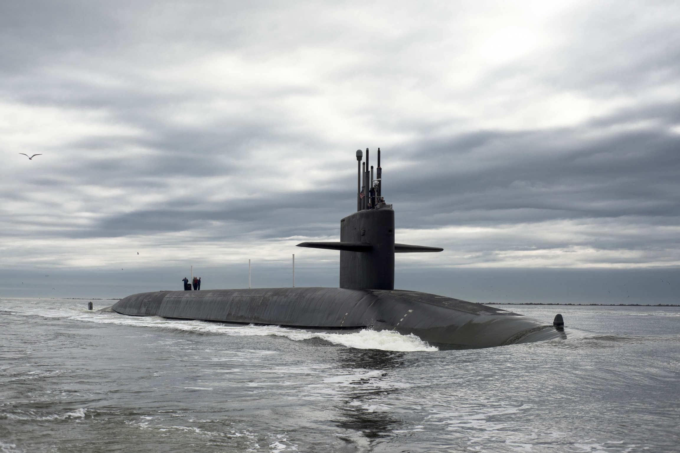 Top of grey submarine sticks out above the water.