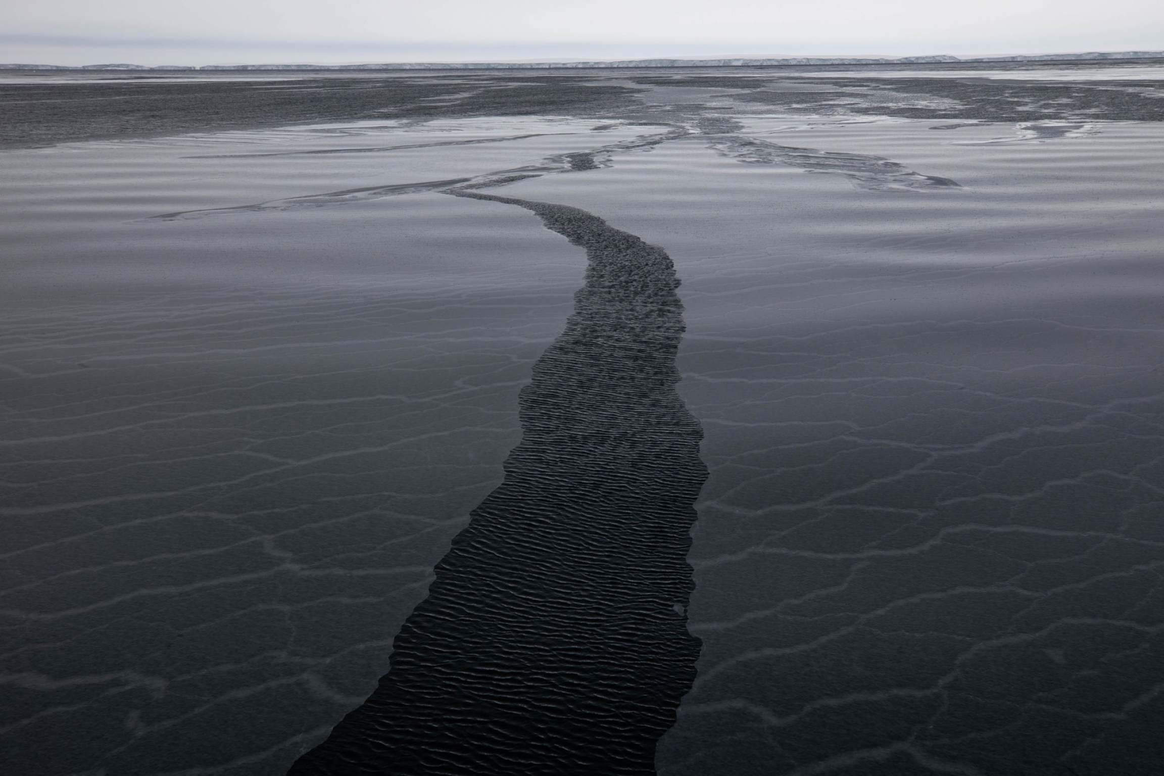 A narrow break in new ice is shown in the middle of the photo on a gray day in the Amundsen Sea.