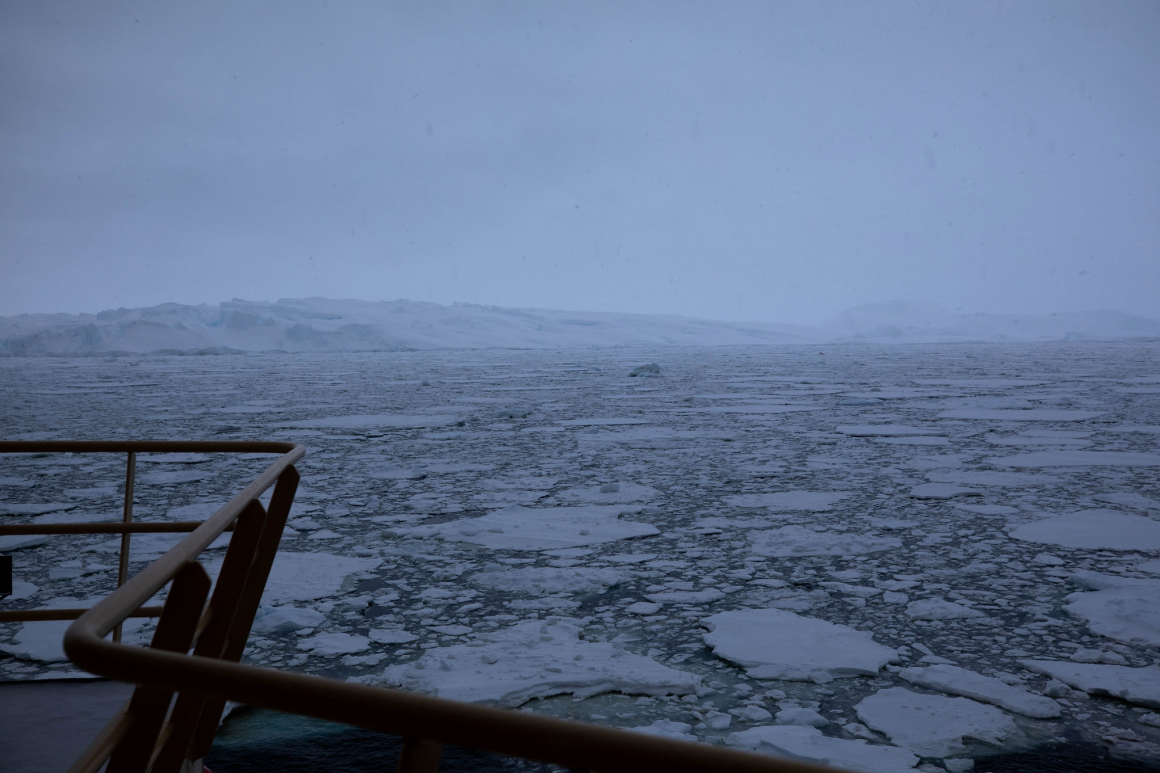 The brown railing of the research vessel is shown in the near ground with larger pancake ice formations in the Amundsen Sea.