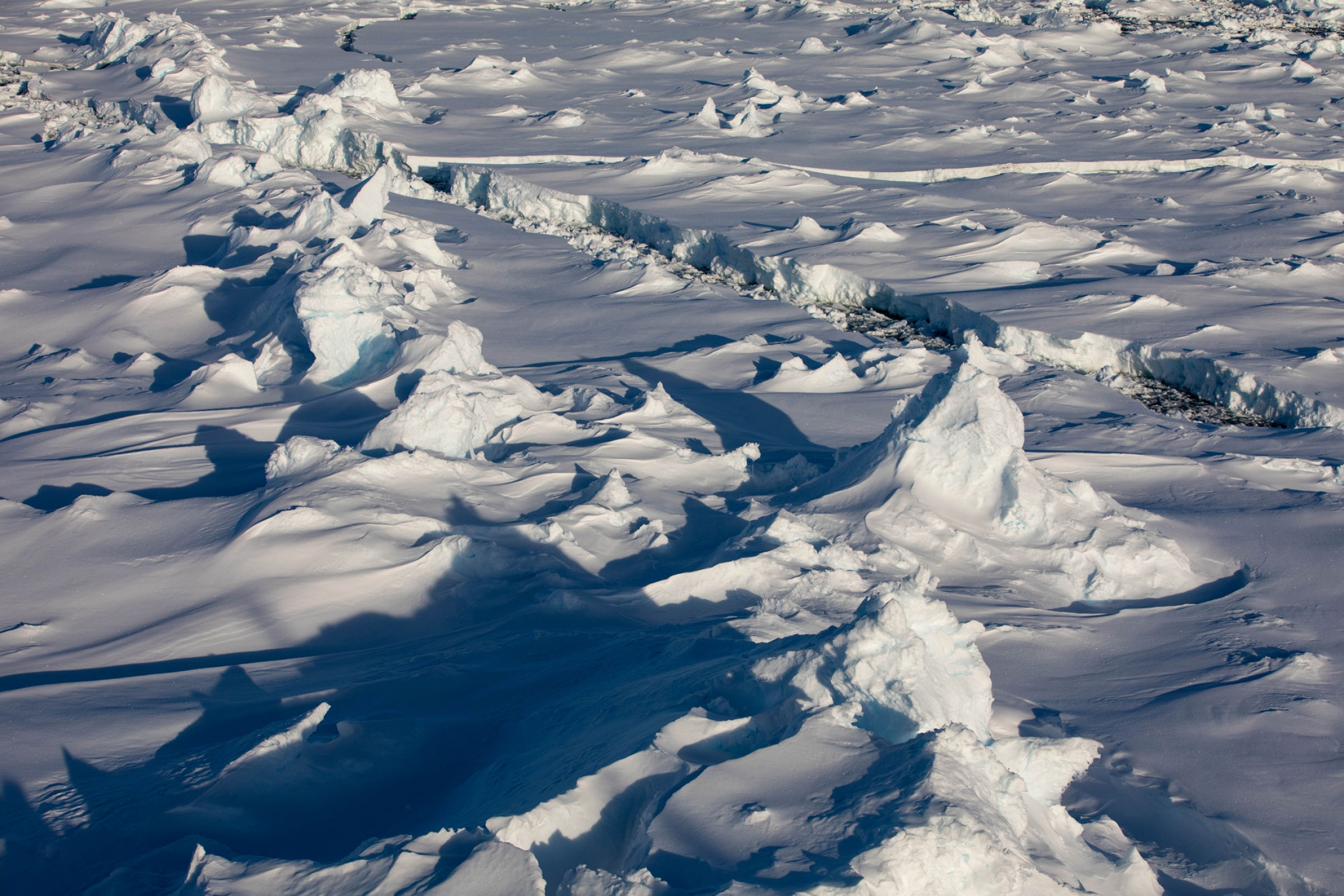 As it ages, large white pieces of ice crash into each other to form pressure ridges in a photo with a thin water path through the two sides.