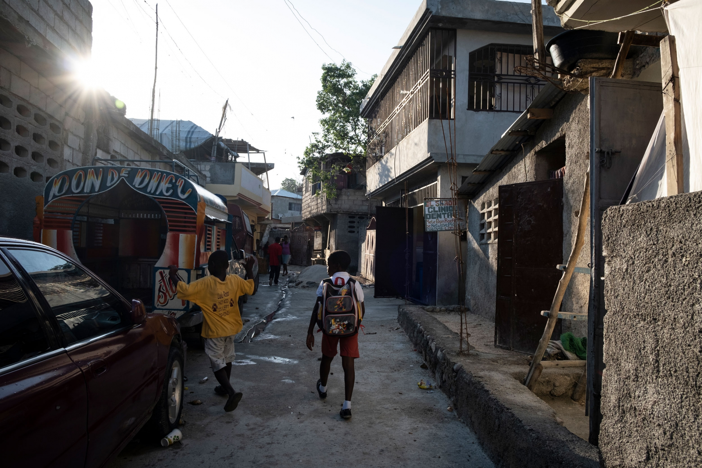 Two children, one with a backpack, are shown walking through a neighborhood in Laboule, outside of Port-au-Prince, Haiti.