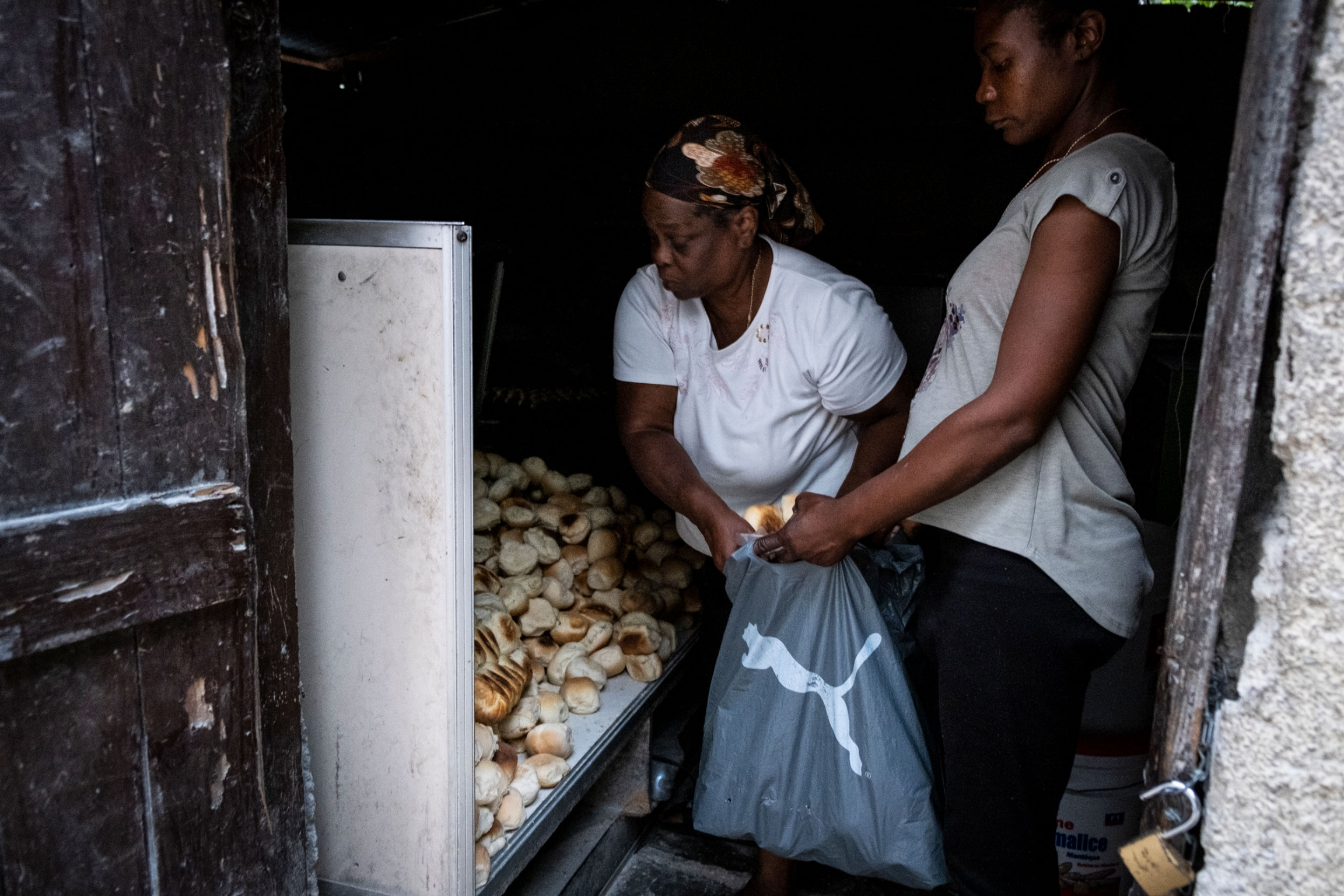 A woman is shown leaning over helping another woman load with biscuits into a plastic bag.