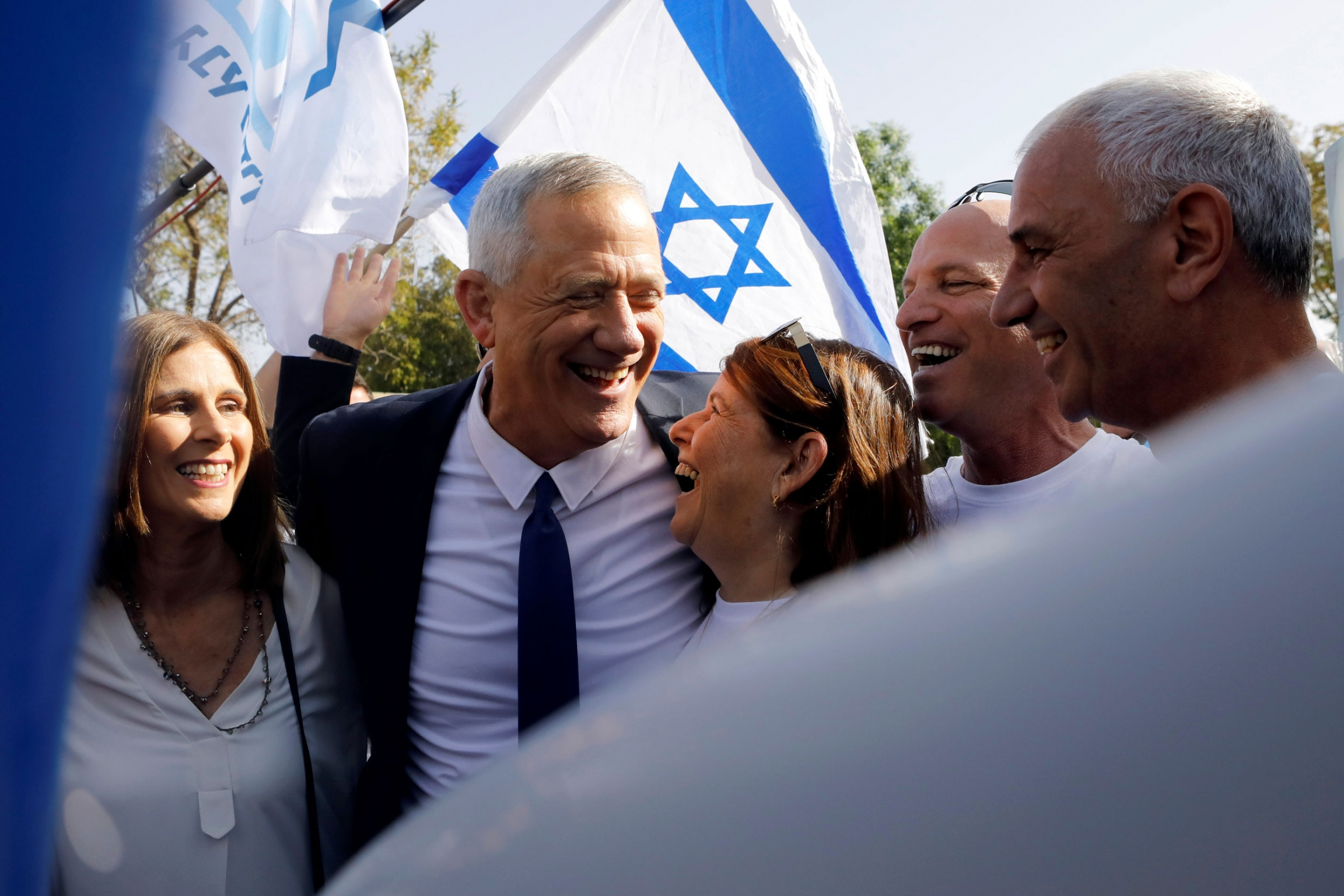 Benny Gantz is shown hugging his wife under his arm and an Israeli flag held behind him in the background.