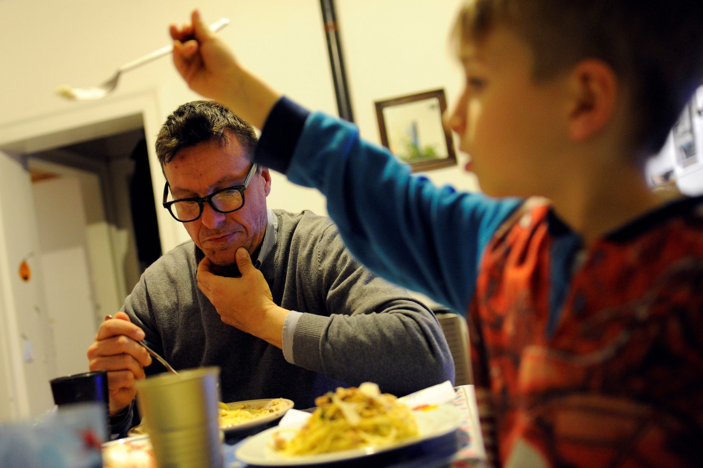 A young boy is shown in the nearground of the photo holding up a fork with his father sitting in the background eating from a plate of food.