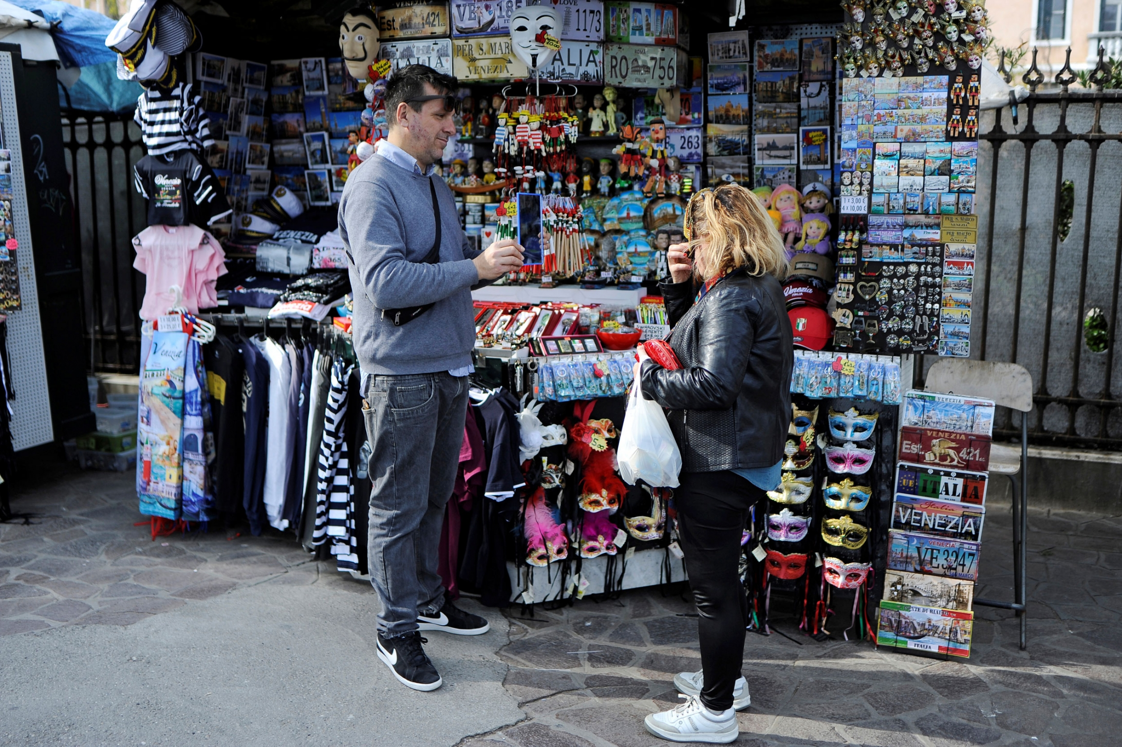 A man in a gray sweater is shown standing next to a souvenir stand helping a woman customer.