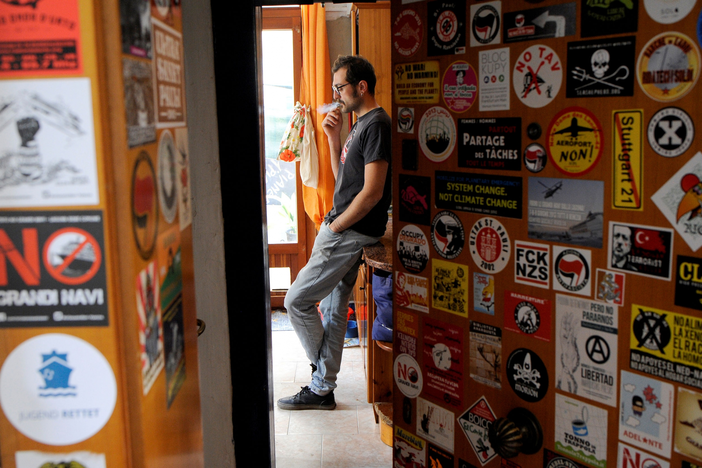 A man is seen through a sticker-covered doorway, leaning up against a dresser and smoking a cigarette.