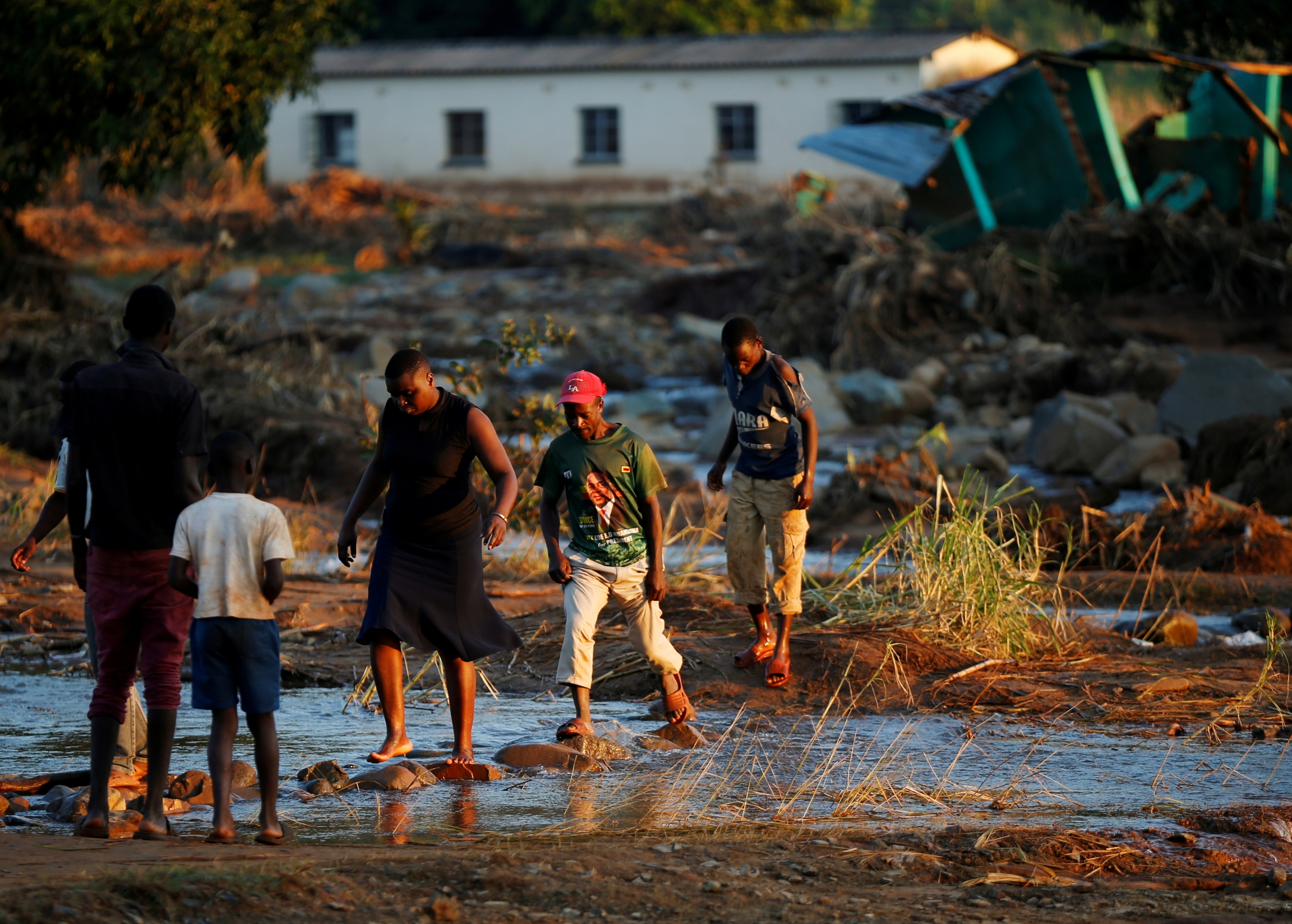Survivors of Cyclone Idai walk through flooded waters to business center to receive aid.