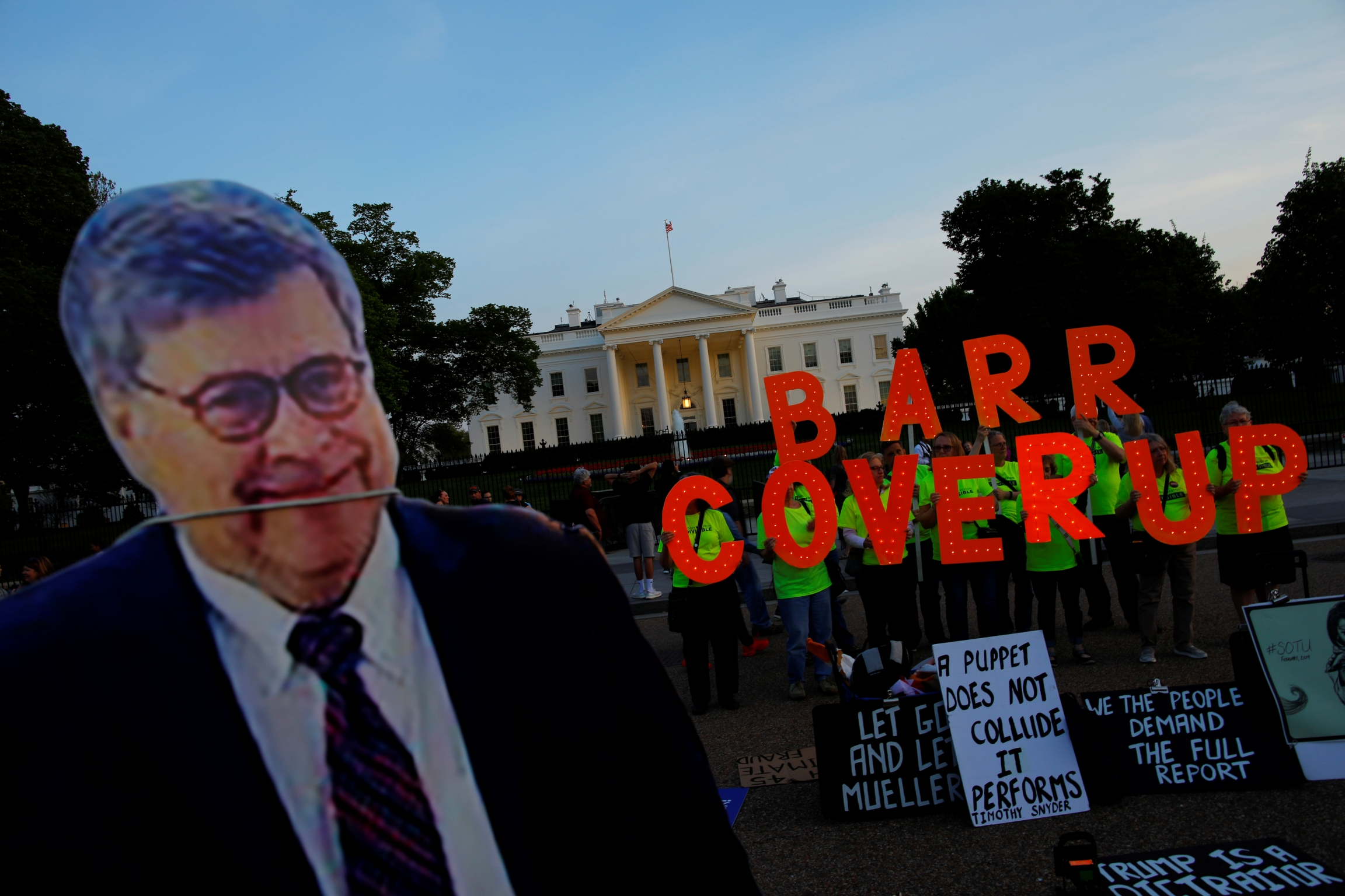 "A cardboard cutout of US Attorney General William Barr is seen as protesters hold signs which read ""Barr Coverup,"" following the release of the Mueller report on President Donald Trump at the White House in Washington, DC, April 18, 2019."