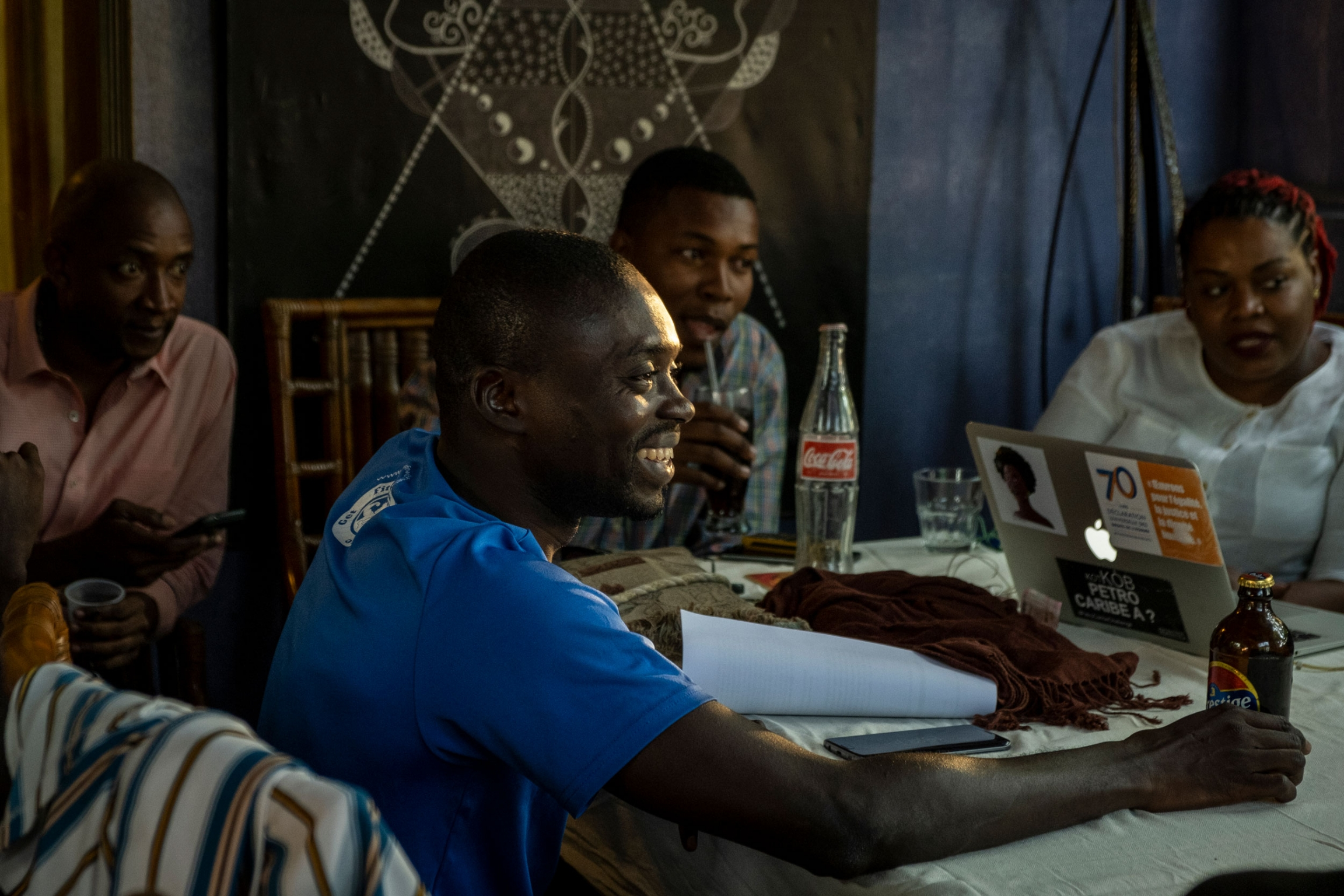A group of young Haitians are shown sitting around a table with computers, Coke and beer bottles on top.