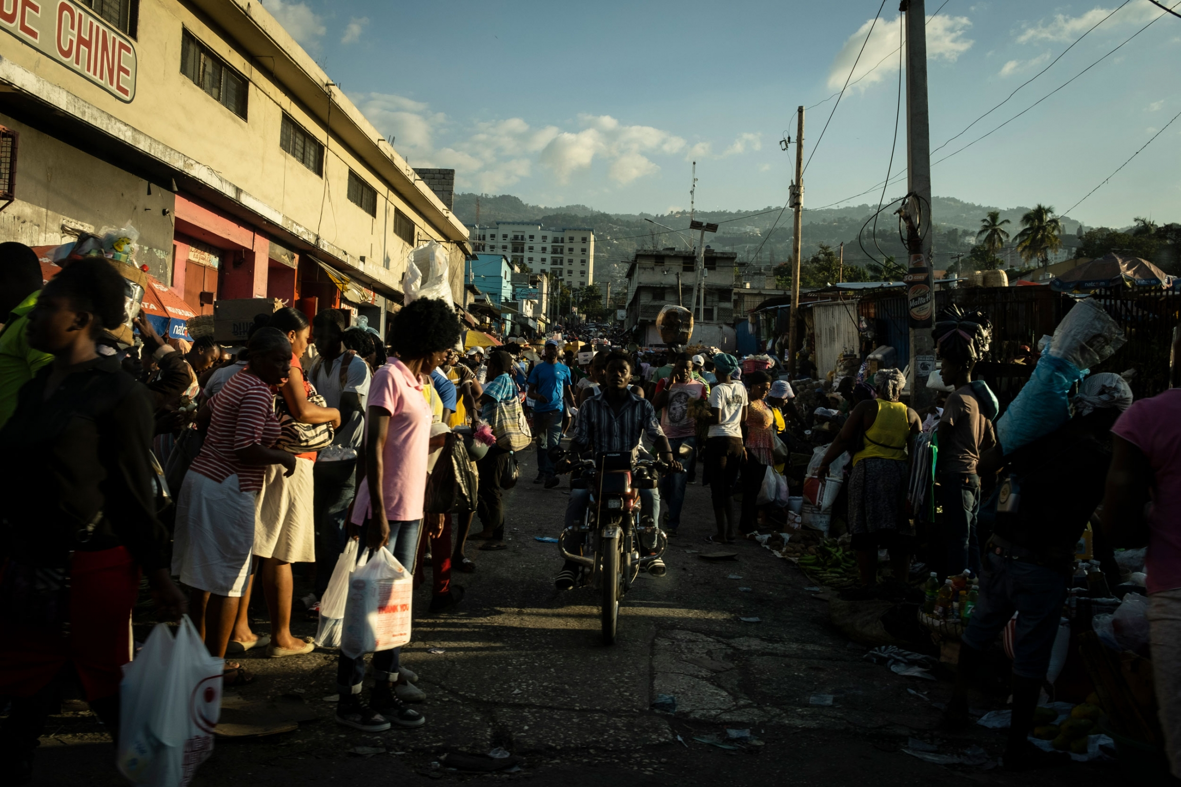 A crowd of people are shown at a Haitian market in Port-au-Prince with a person on a motorcycle in the middle.