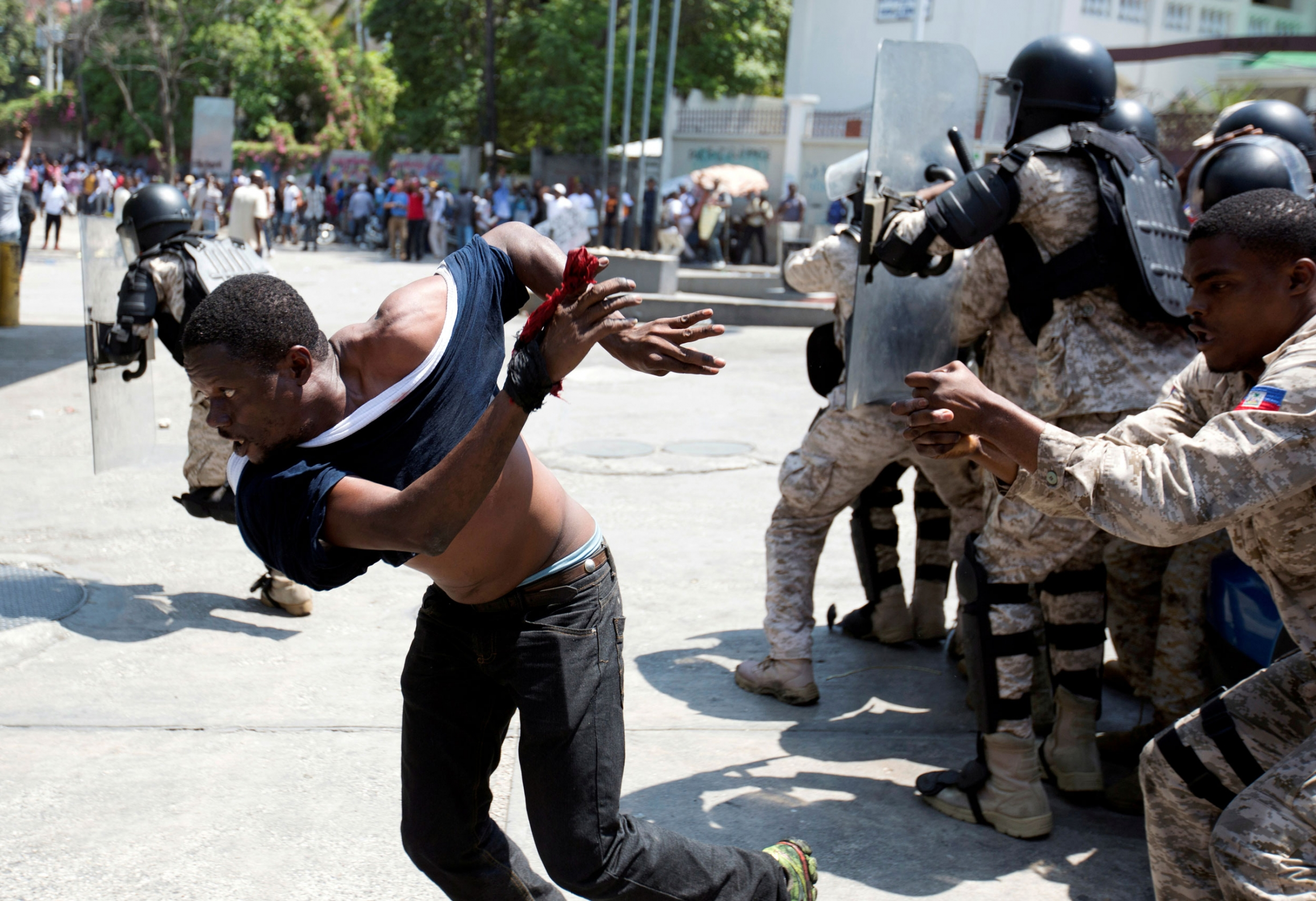 A demonstrator is shown running from Haitian security authorities with his blue shirt almost torn off.