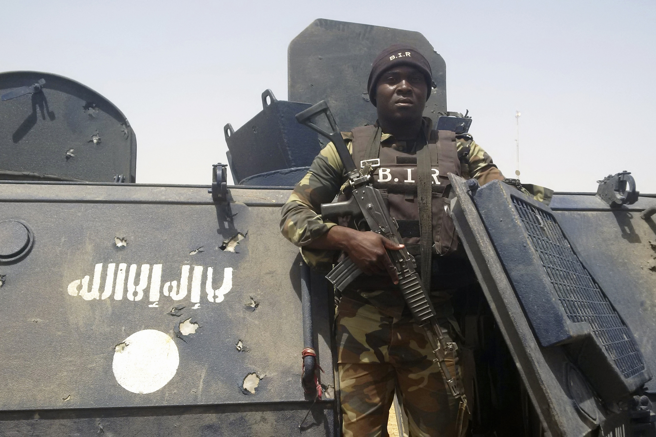 Cameroonian soldier stands near tank with Boko Haram logo on it.