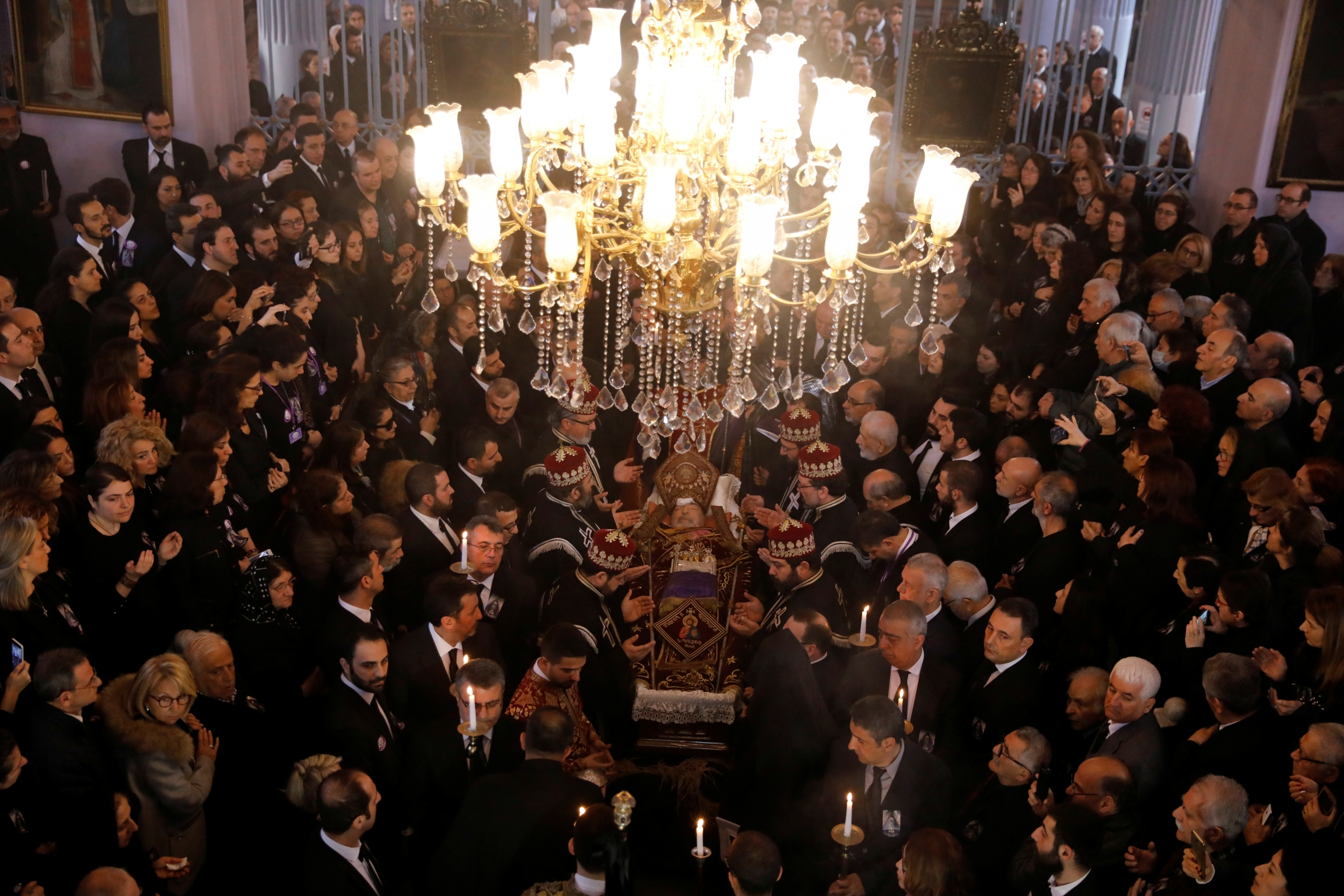 Mourners in black for Armenian Patriach stand under huge chandelier in church.