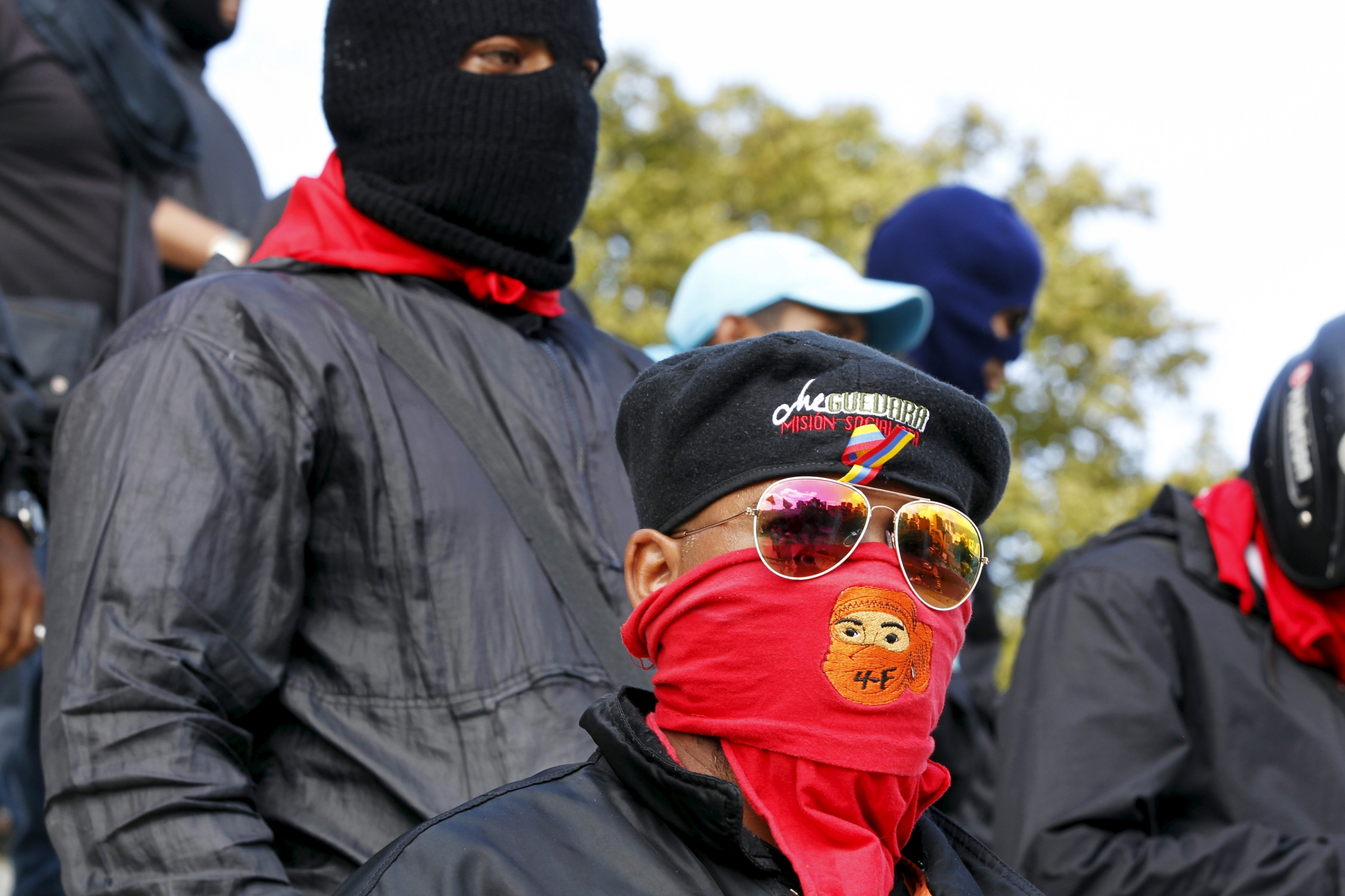 A man wears a red mask over his mouth and sunglasses