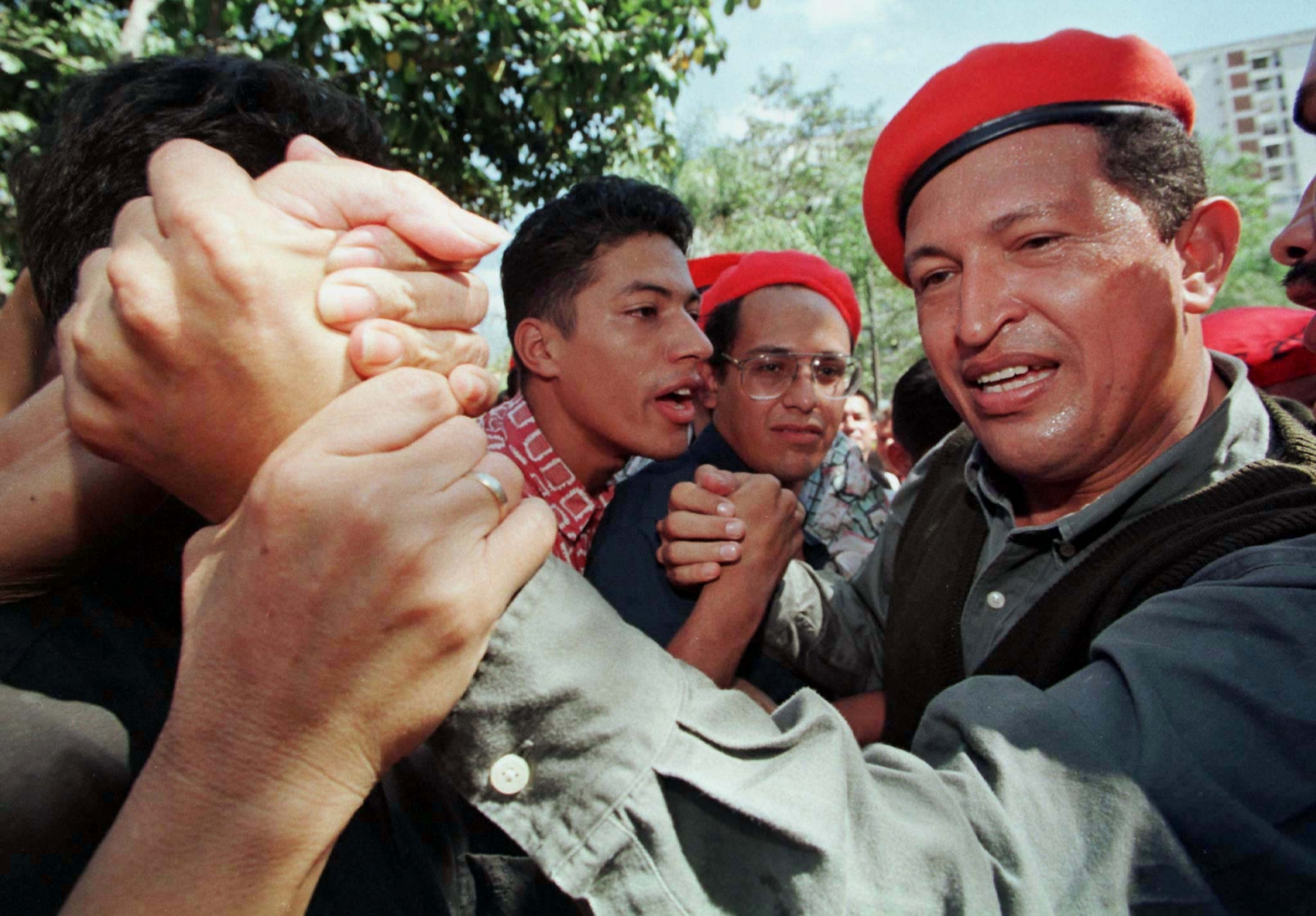 Chavez wearing red beret shakes hand of supporter