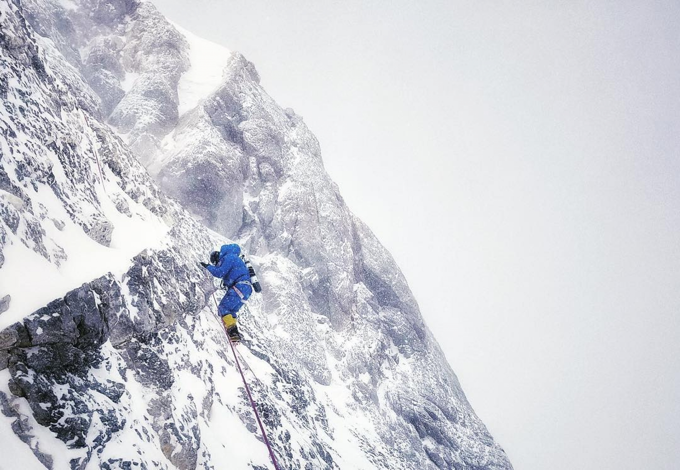 A person wearing blue mountain climbing suit and yellow boots climbs a rocky face on Mount Everest