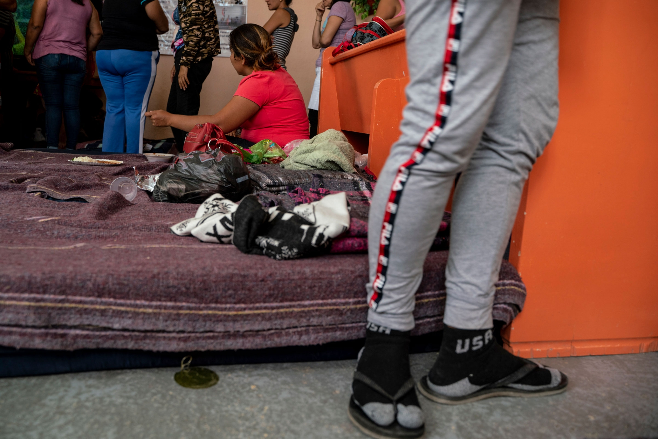 A mattress sits on the floor as people stand around a room.