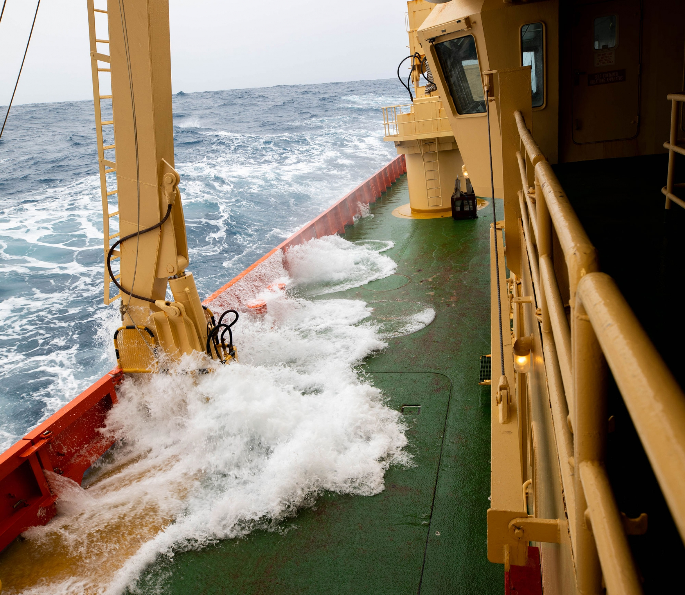 Waves are shown crashing against the side of the ship and spilling water on to the deck.