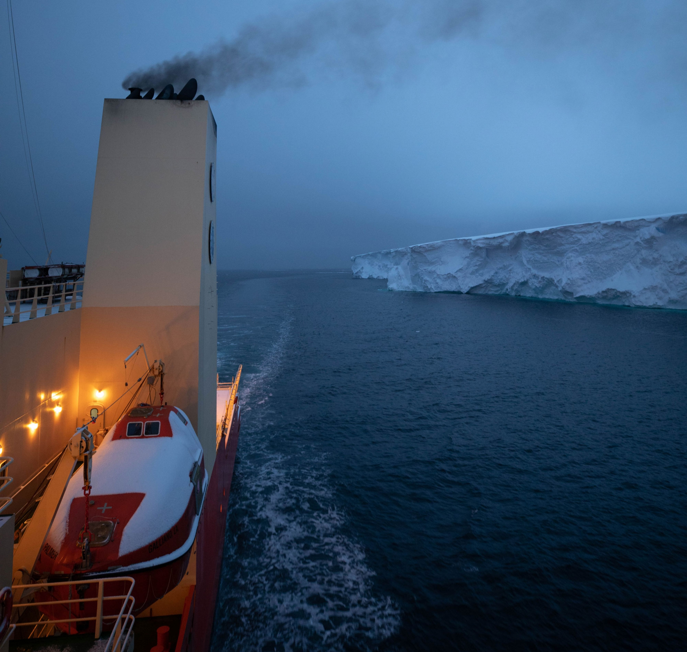 From the side of the vessel, the Nathaniel B. Palmer is shown with a smoke stack in the nearground, navigating along the eastern tongue of Thwaites glacier.