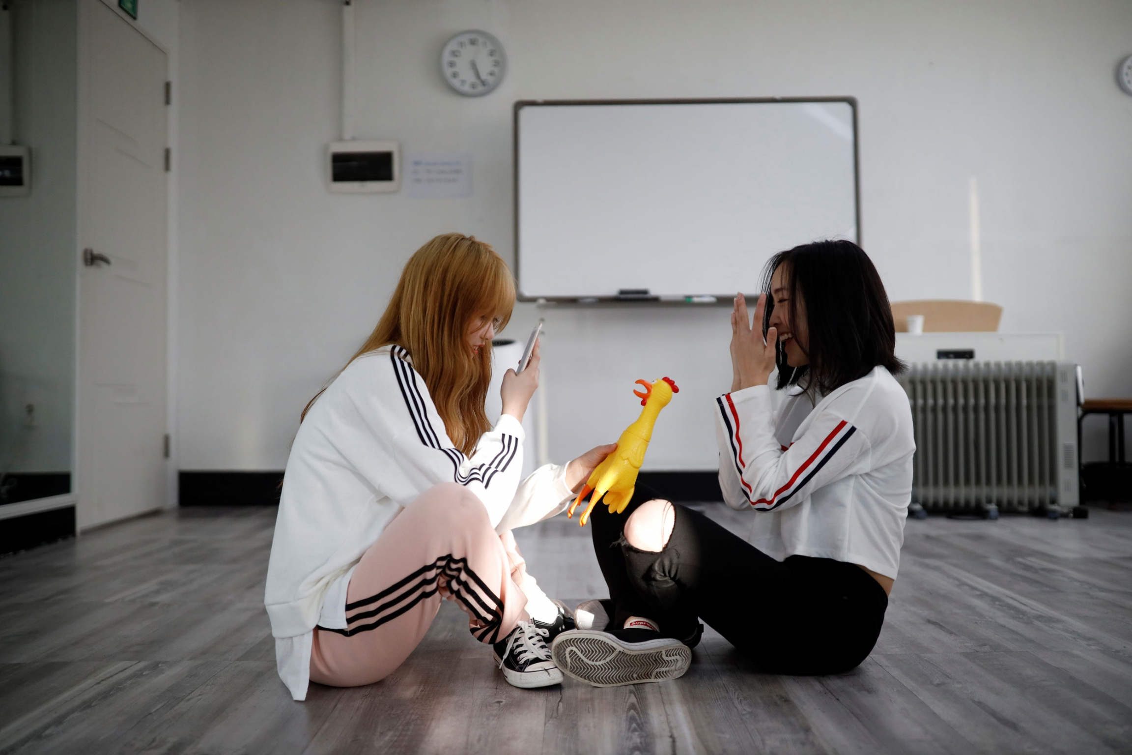 Two young women are shown sitting on the floor with one holding a yellow rubber chicken and taking a photo with her mobile phone.