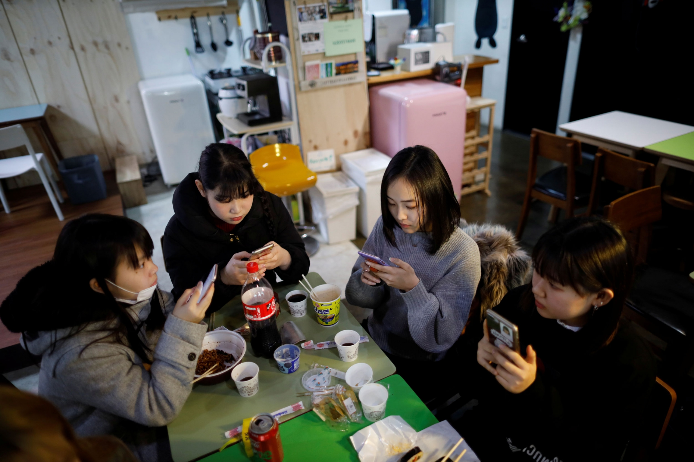 Four young women are shown sitting around two small green tables, all of them with a mobile phone.