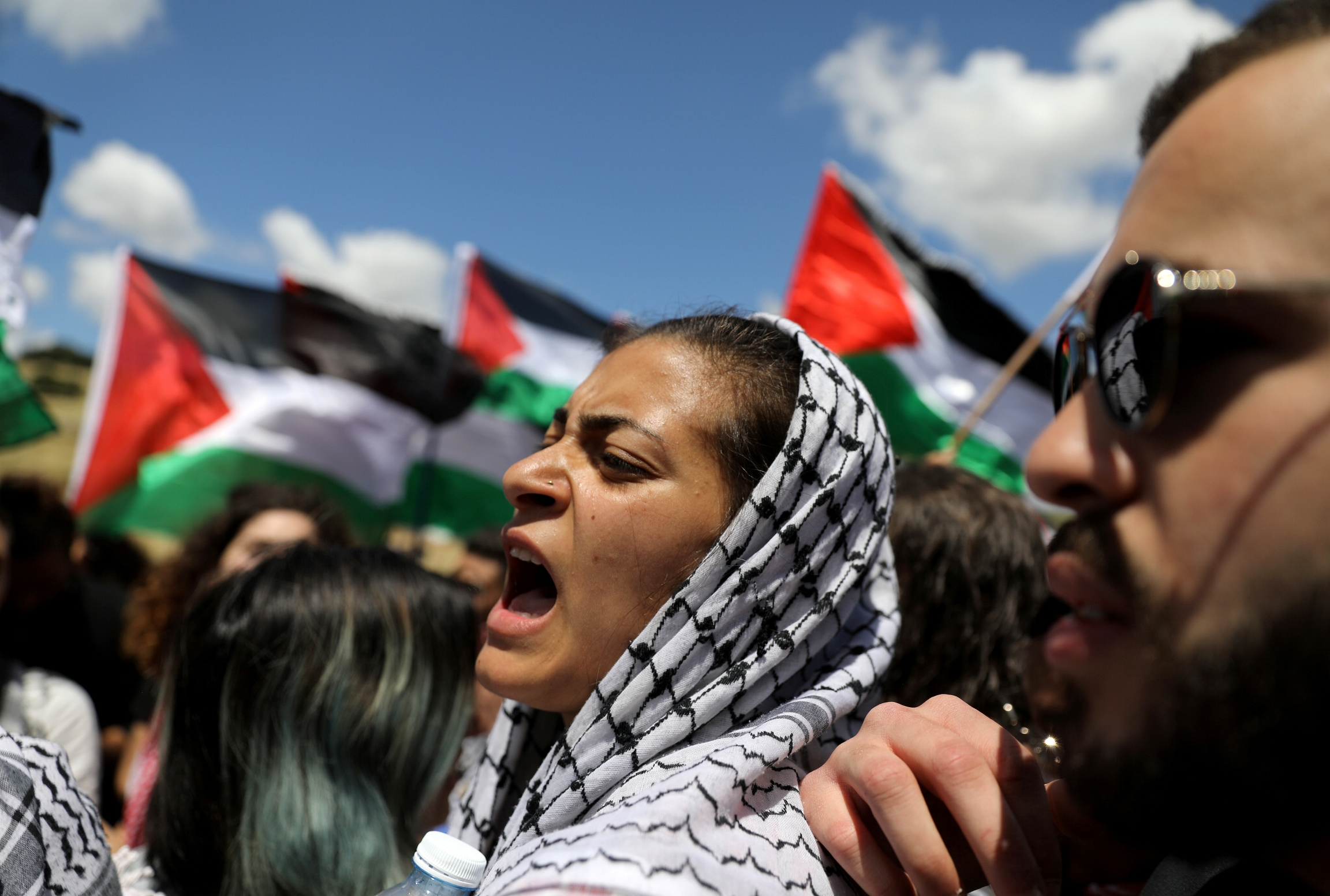 A woman shouts next to protesters holding Palestinian flag.