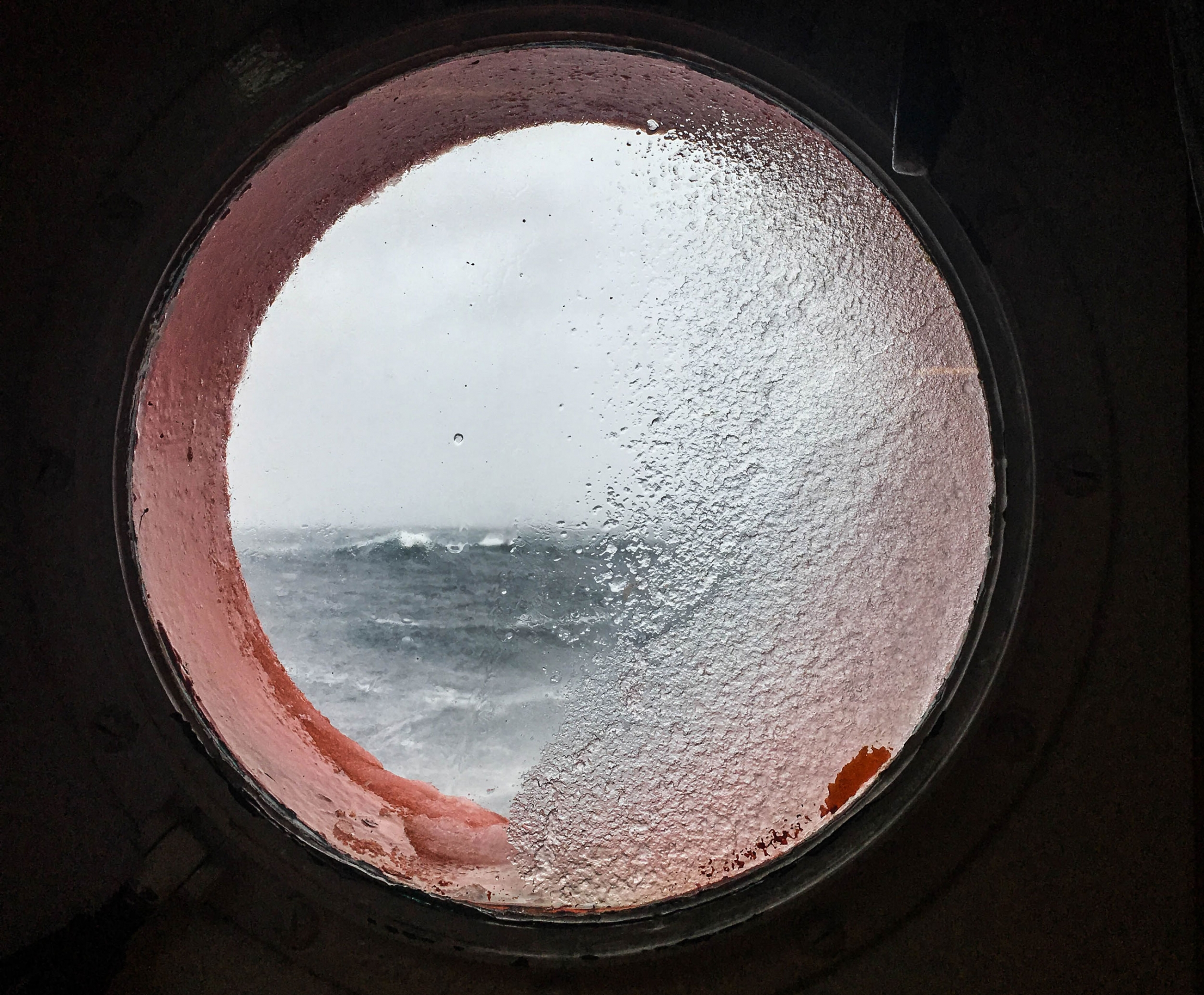 A round window is shown with very choppy waves off in the distance.