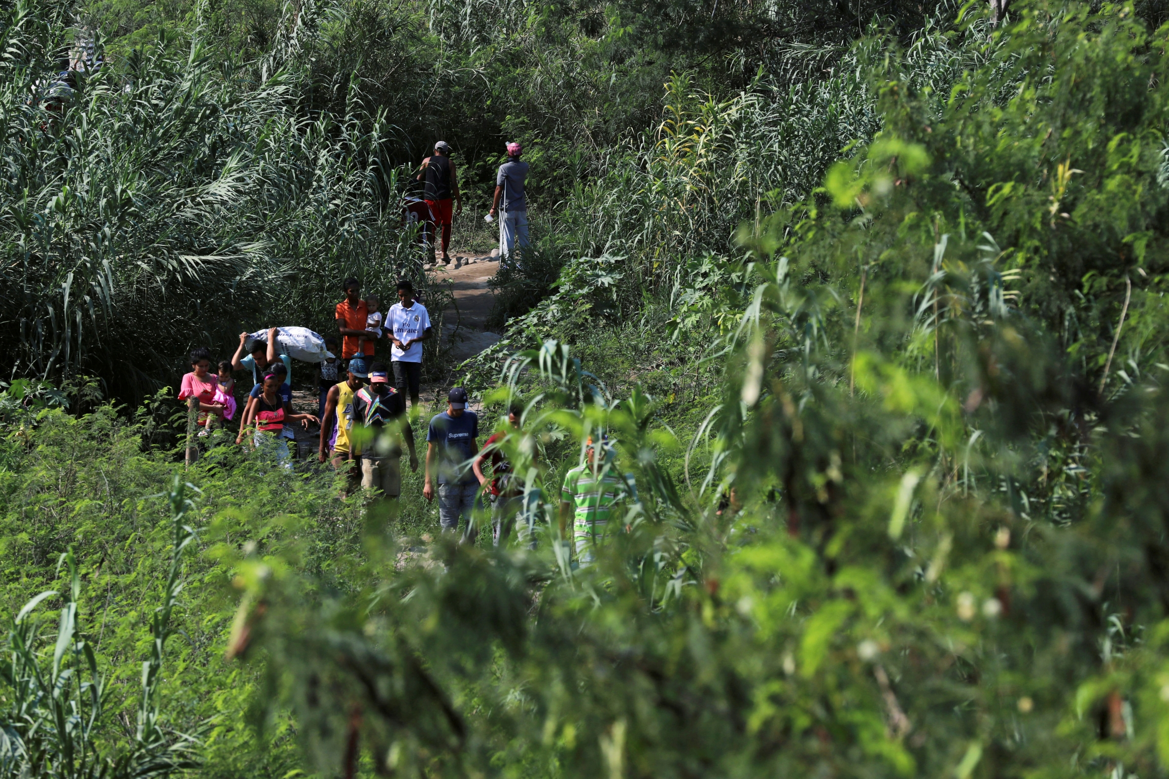 people walk along a path on the  venezuela-colombia border