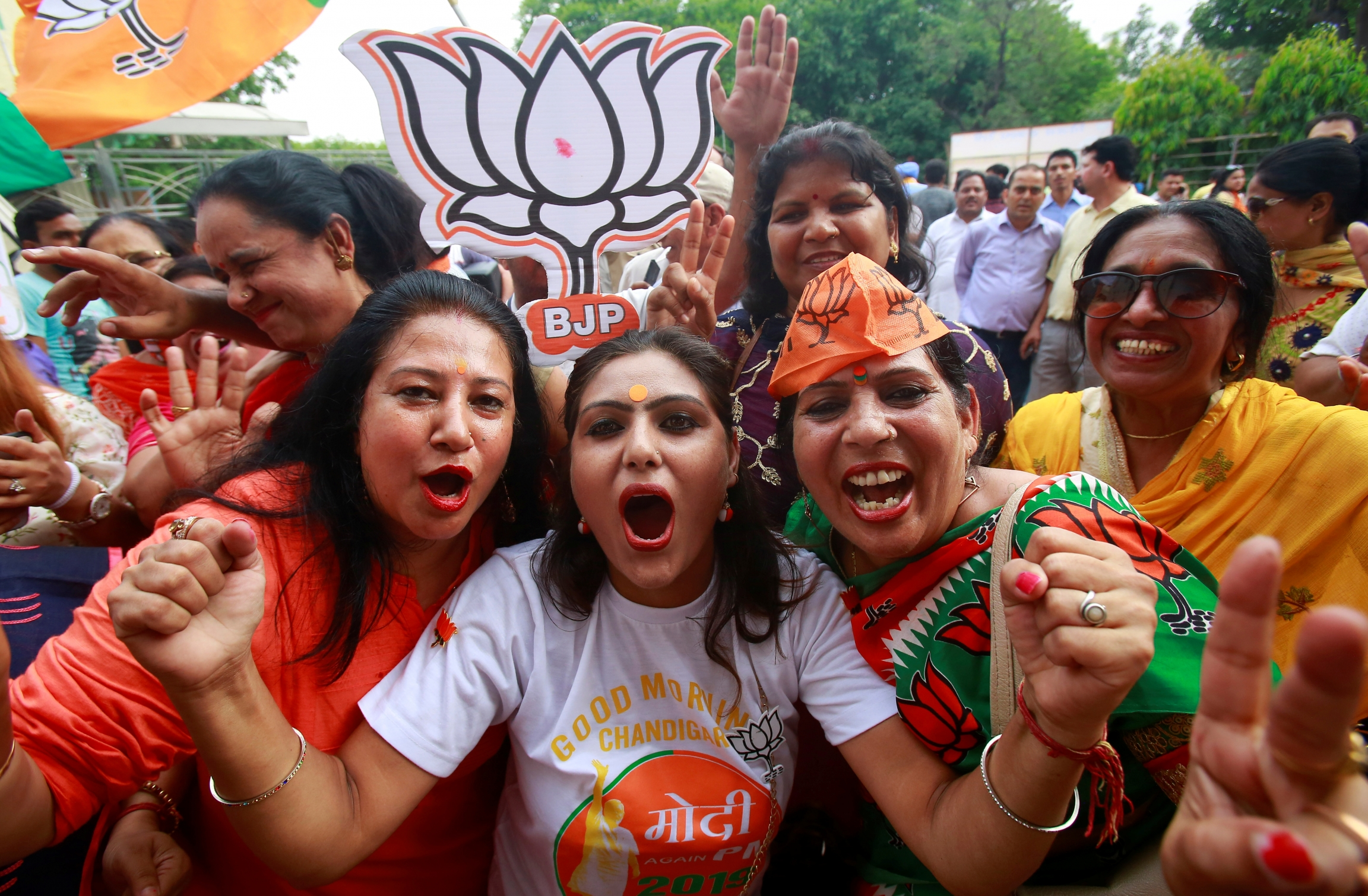 Three women cheer during election results in India wearing orange for BJP.