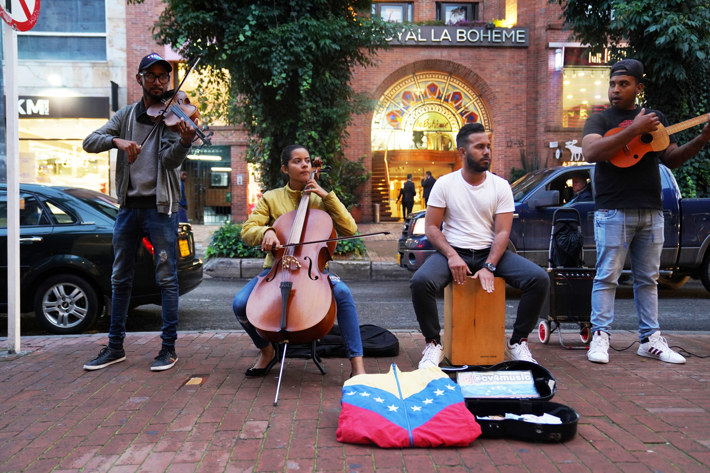 A group of musicians play music on the street.
