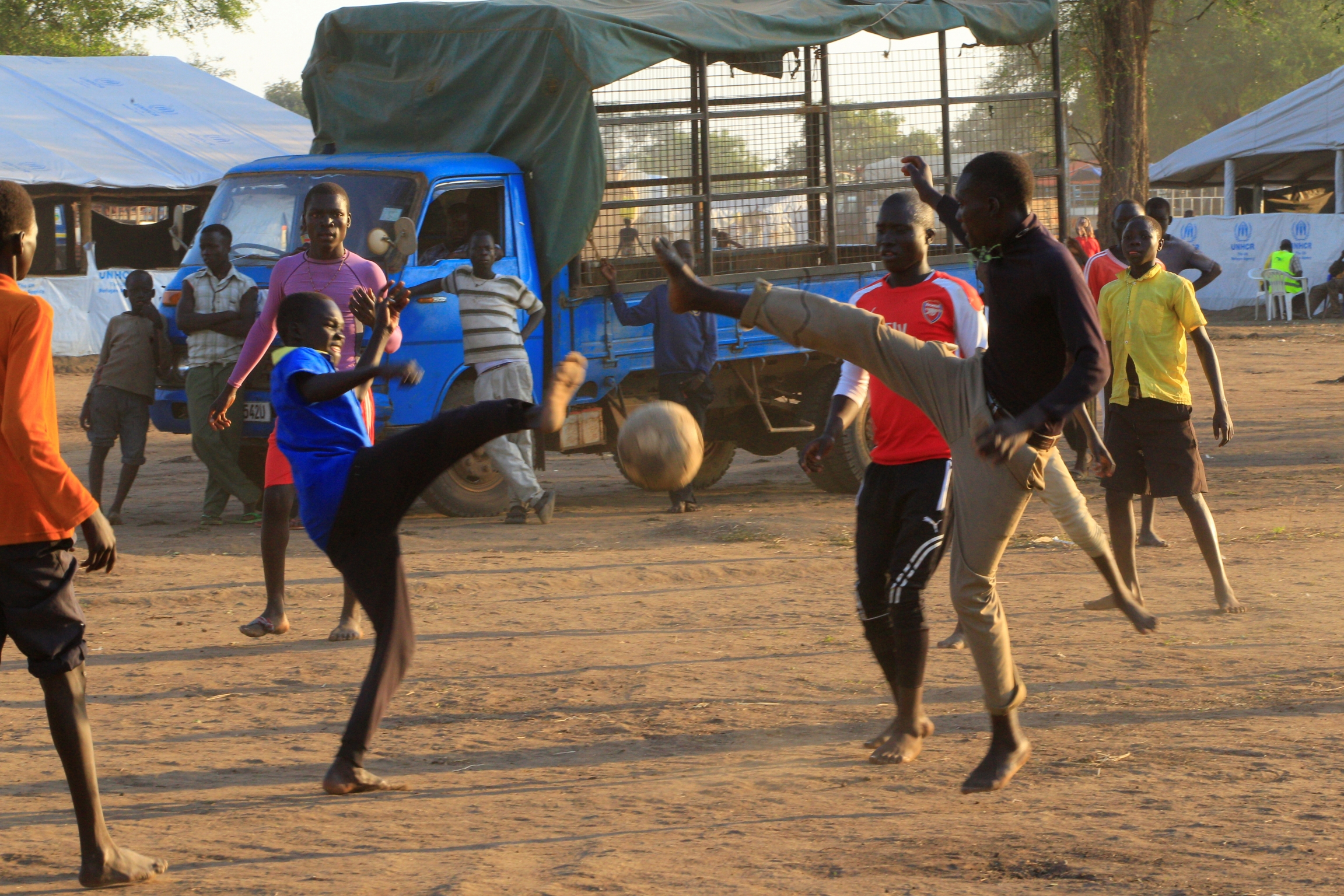 youth play soccer near trucks at refugee camp