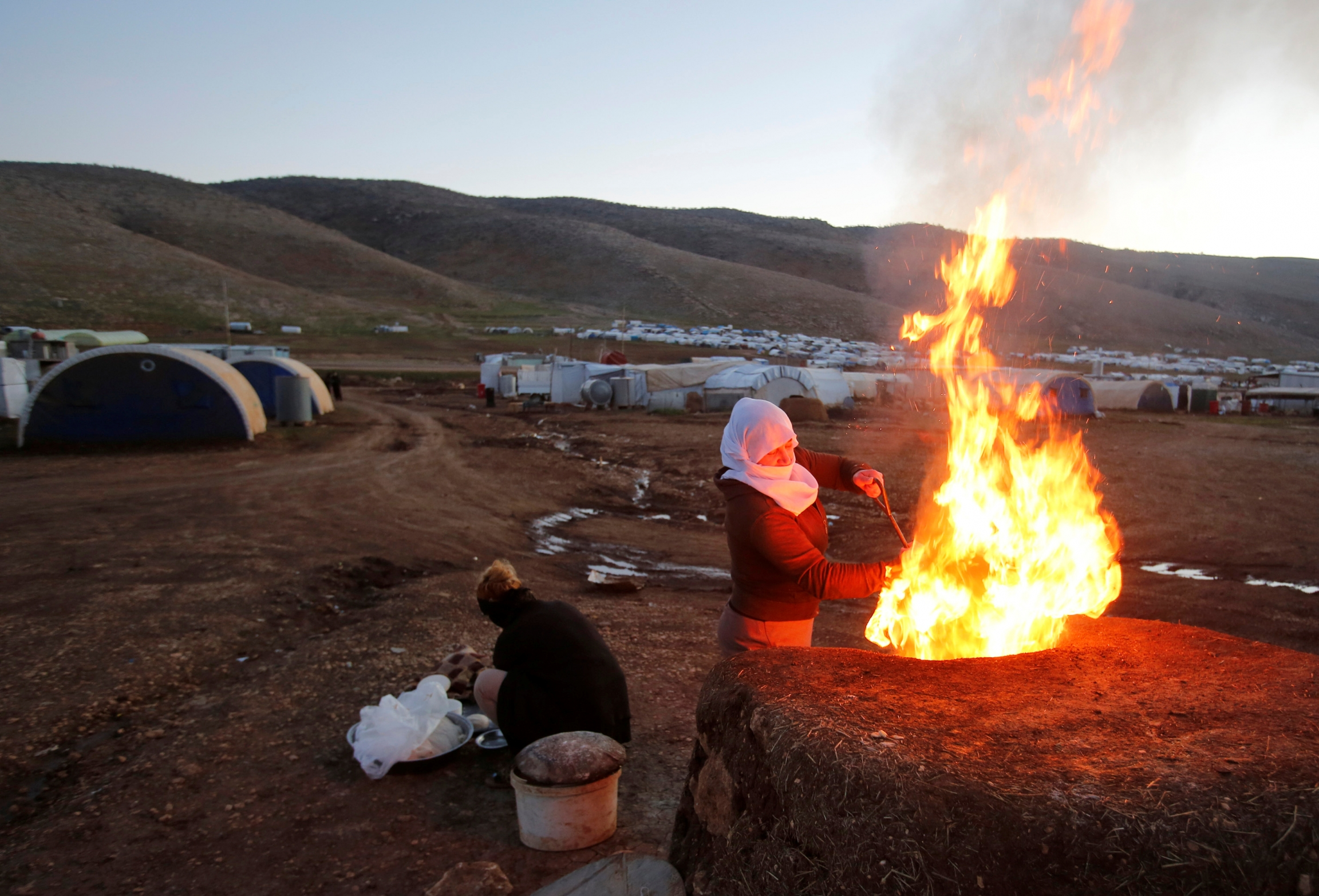 A woman prepares bread with huge fire at refugee camp near white tents.