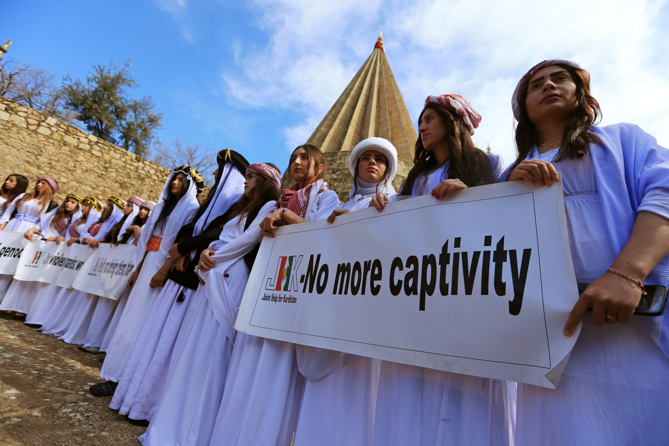 "Women in white robes and turbans carry sign that says ""no more captivity."""