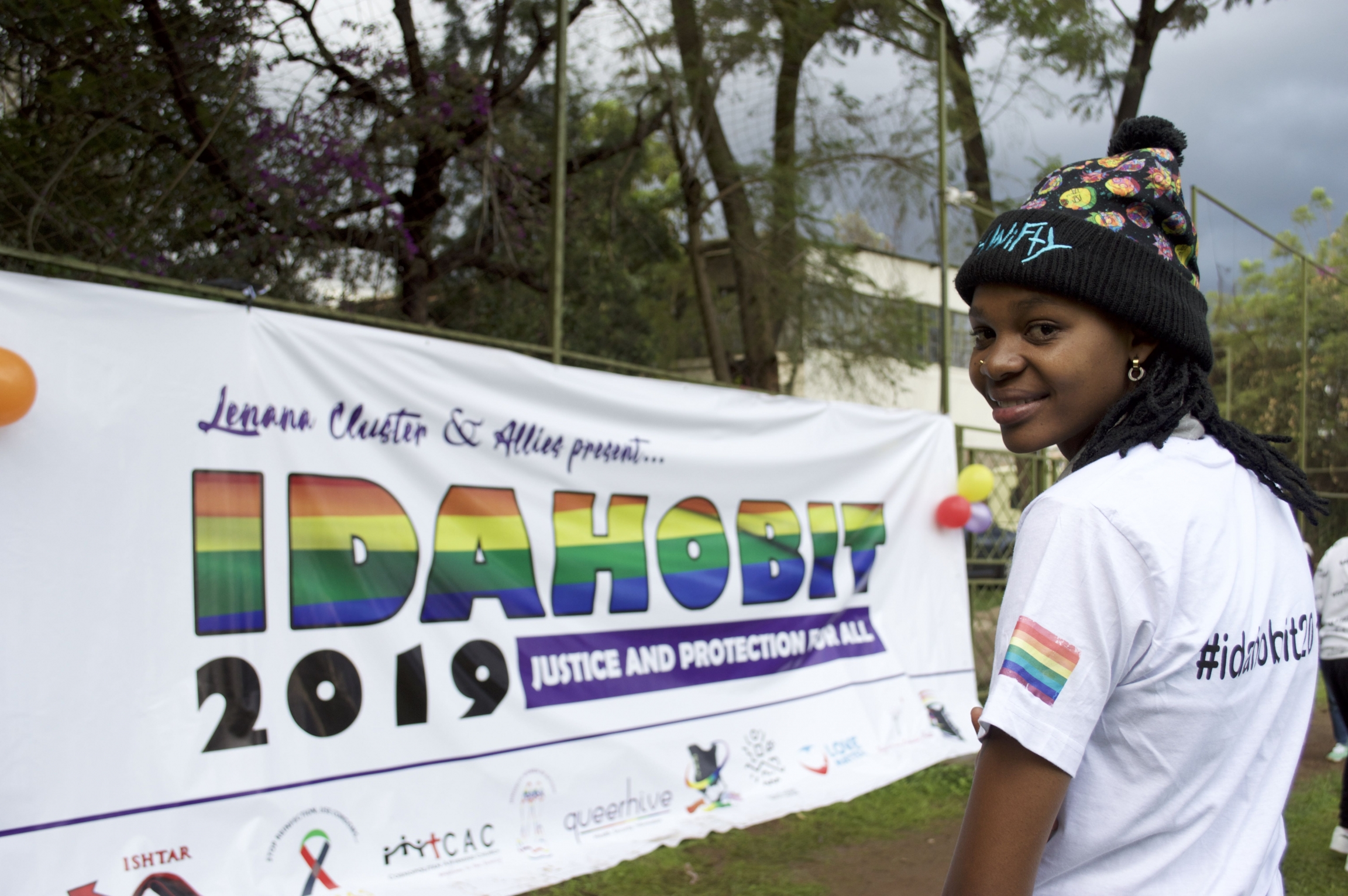 A queer person in Kenya stands near rainbow banner.