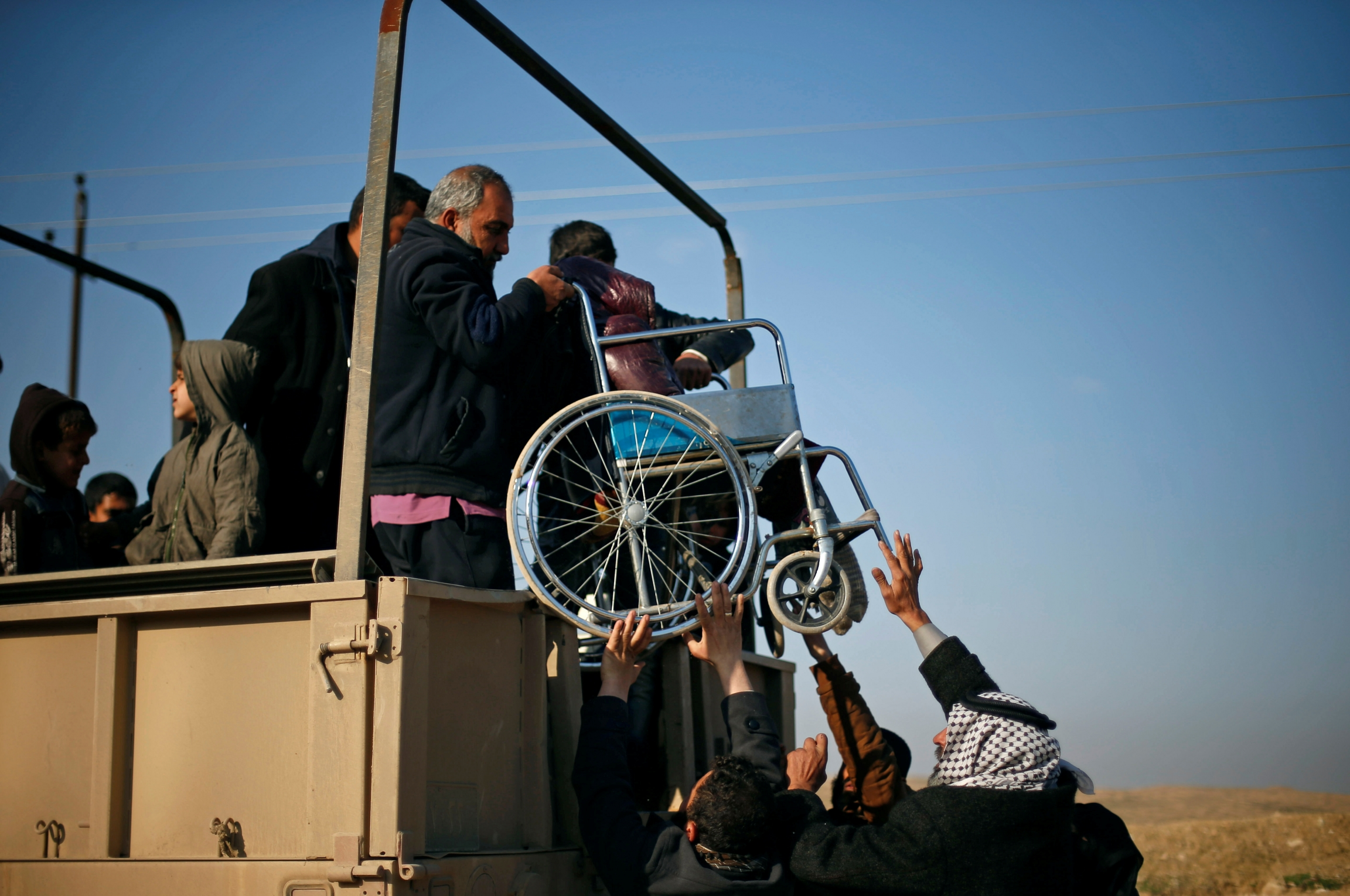 A wheelchair is lifted onto truck as refugees flee